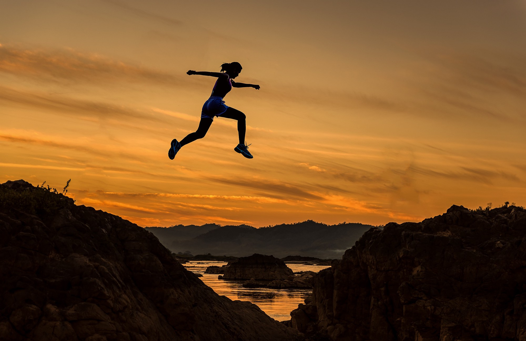 Woman jumping high between two hills, silhouetted against a sunset.