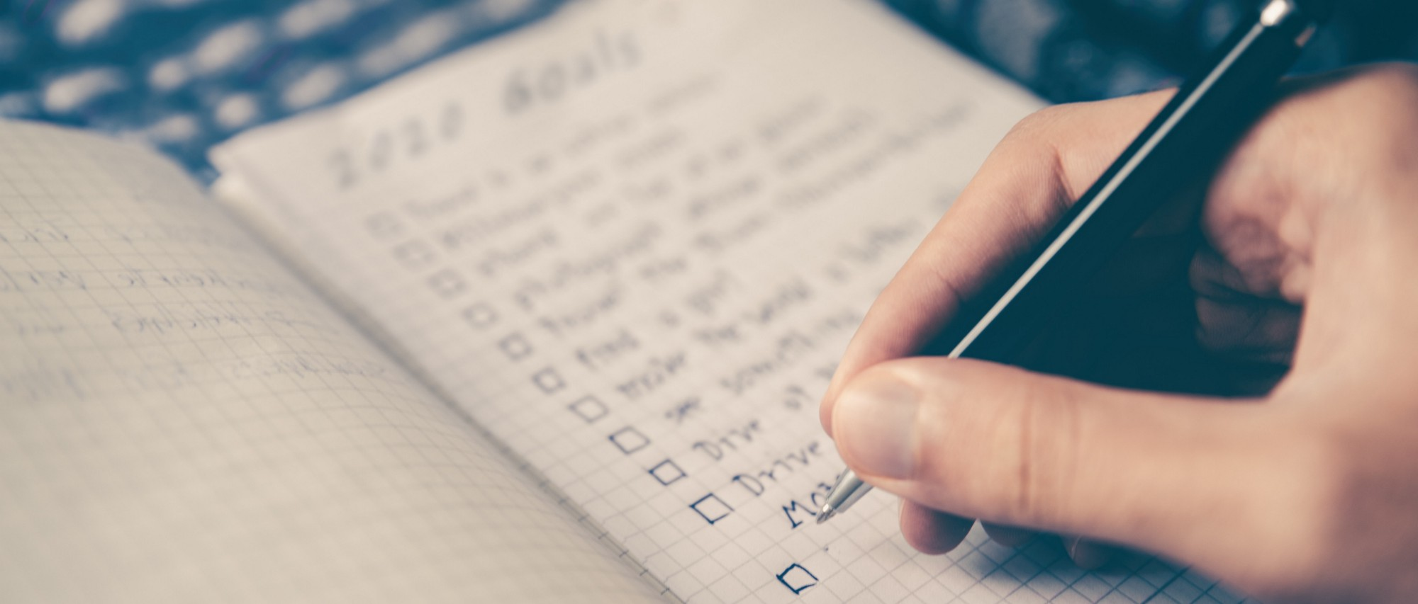 Someone writing a checklist of goals
