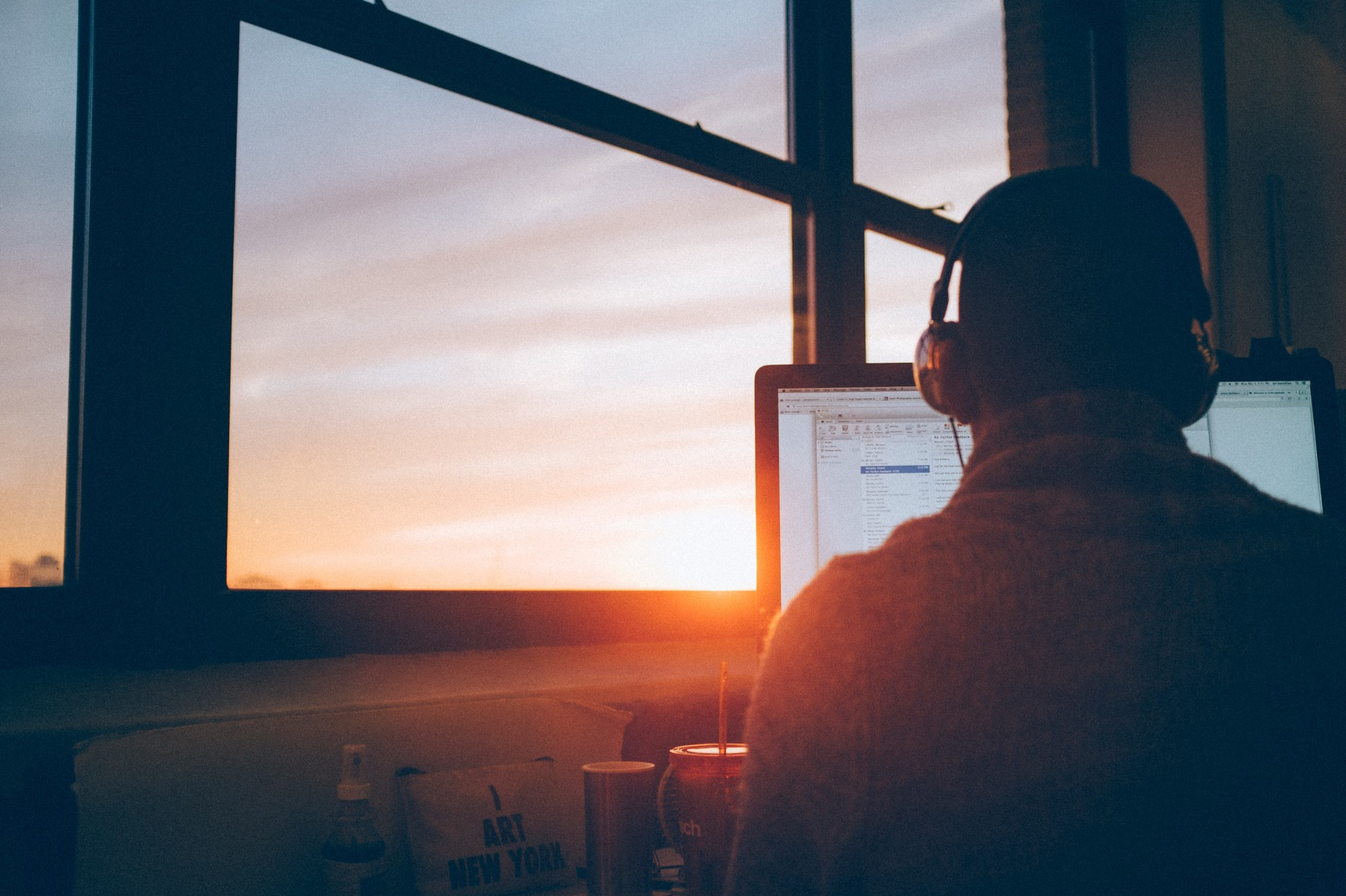 Man with headphones working on a laptop by a window at sunset.