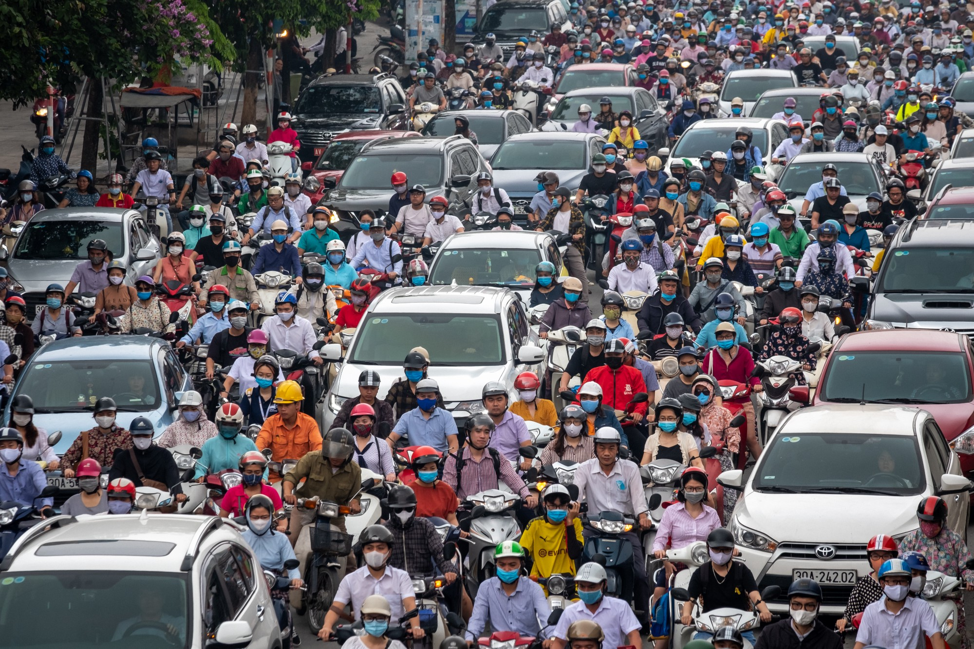 Motorbike riders with face masks are stuck in traffic during the morning peak hour on May 19, 2020 in Hanoi, Vietnam.