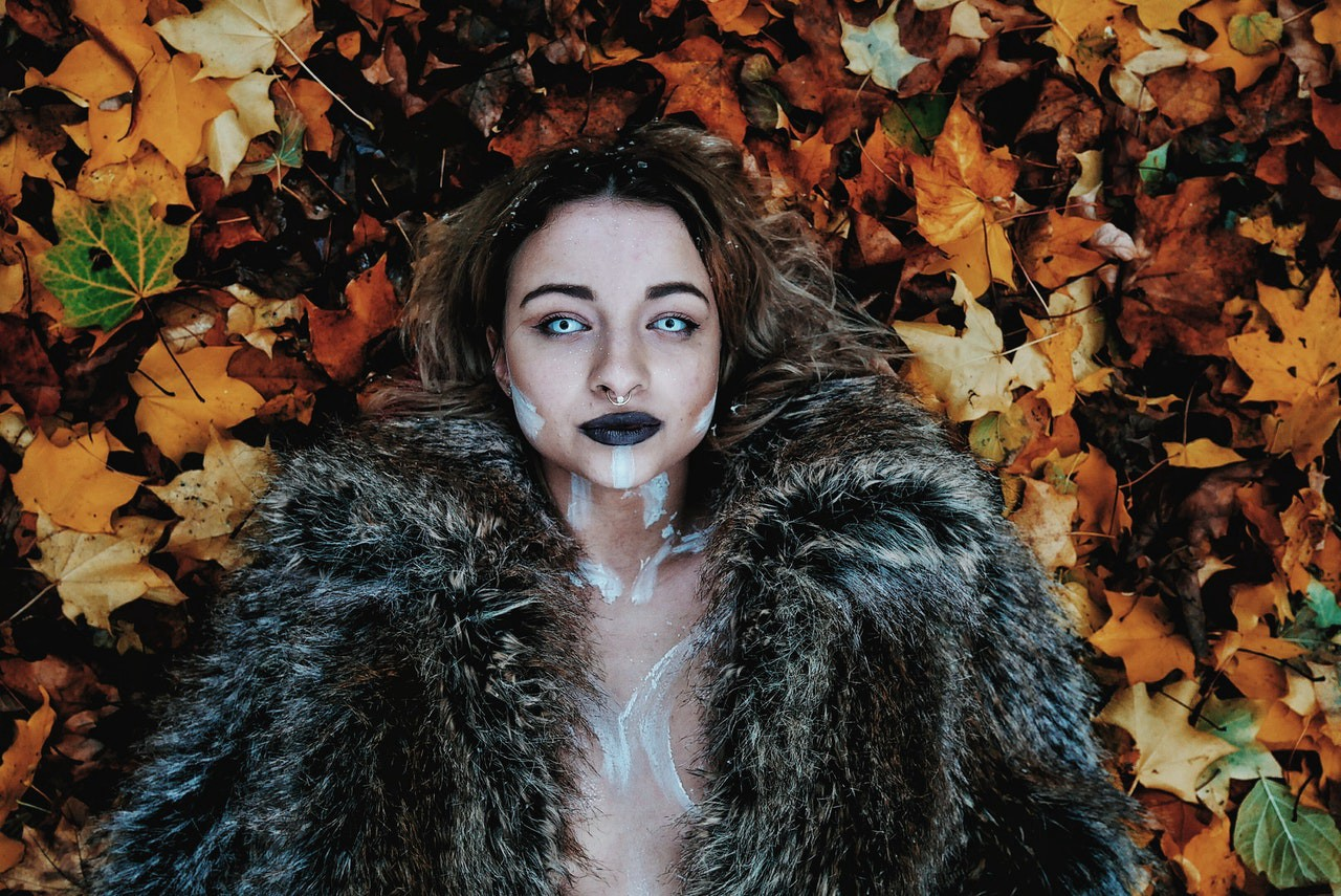 Cold fantasy woman in black fur coat laying on brown maple leaves and staring at you