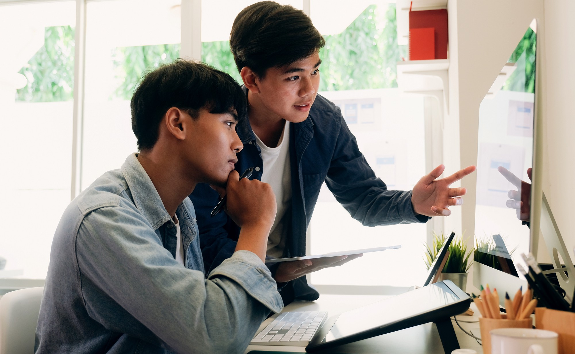 Two young men review a design on a large iMac computer monitor in a bright, sunny room.