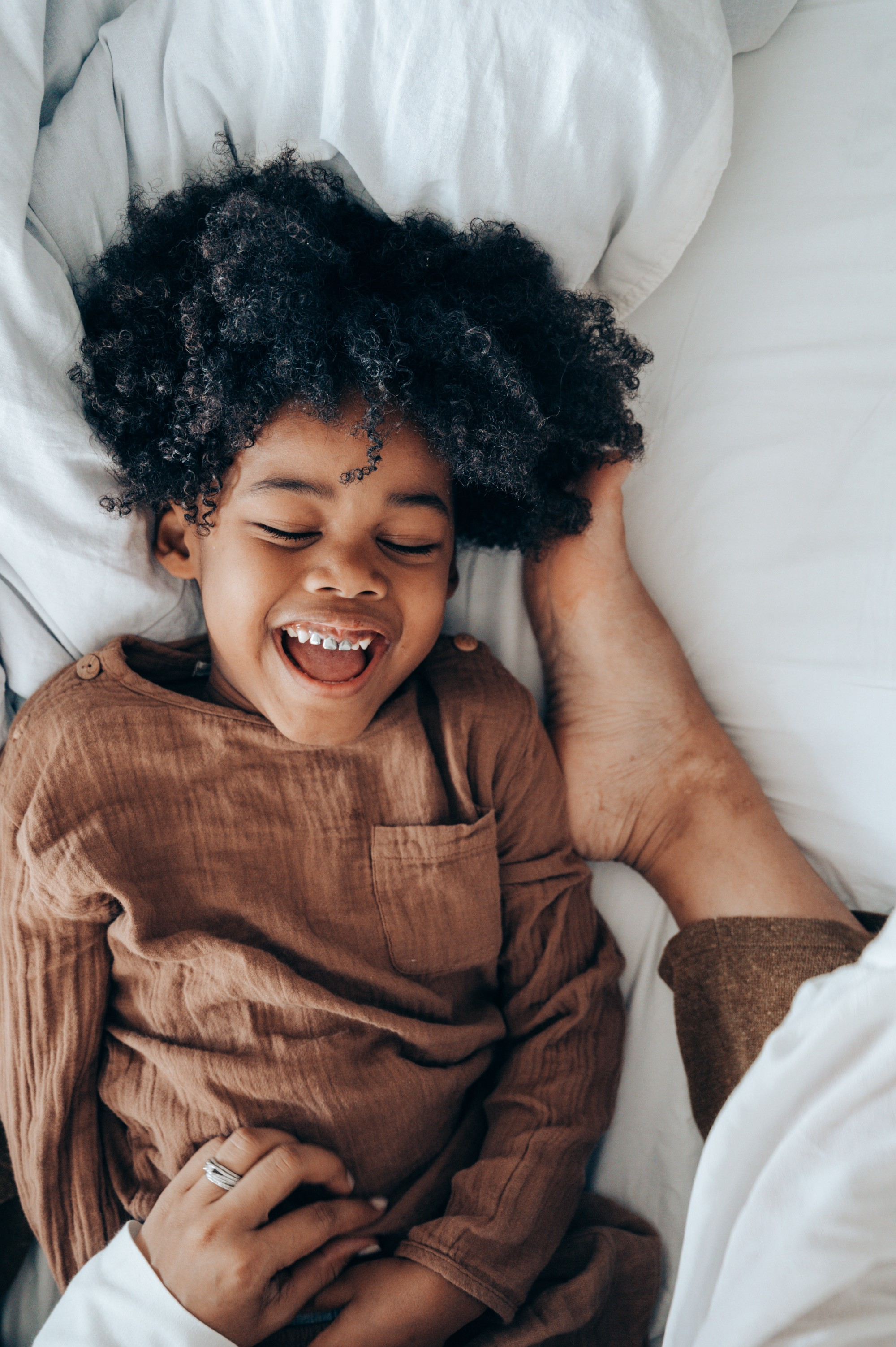 A Black child under five in the bed laughing. It looks like his mother is tickling him.