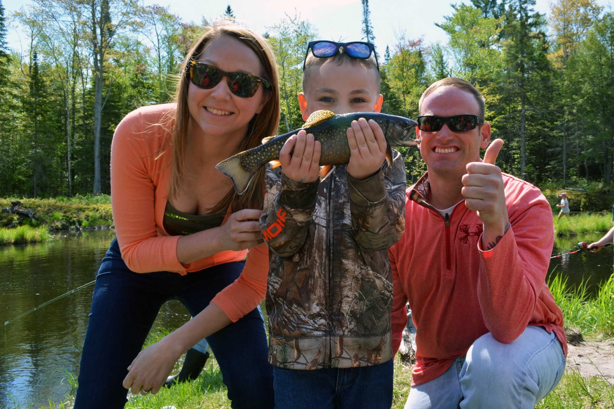 A woman and man pose with a child who is holding a fish. A pond and woods are in the background.