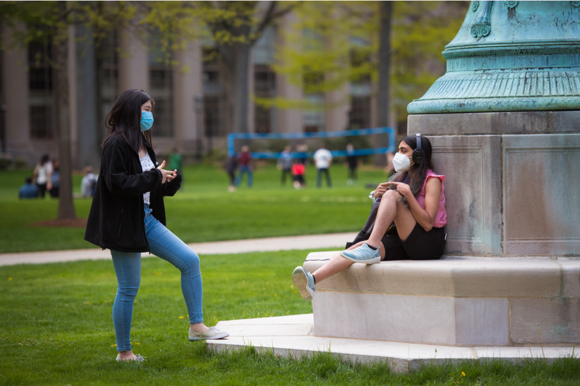 Two students wearing masks talk to each other on MIT campus. One is standing and one is sitting.
