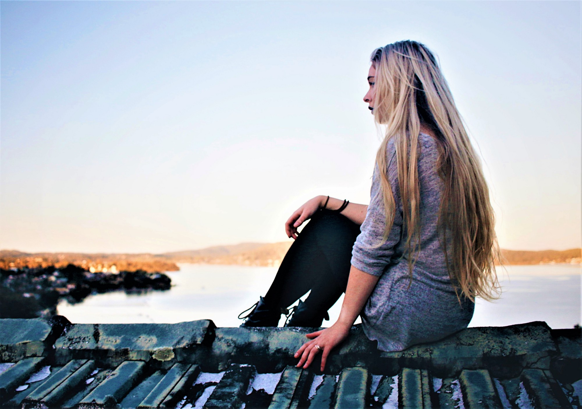 side view of girl with long blonde hair sitting on rustic wooden pier looking out over lake