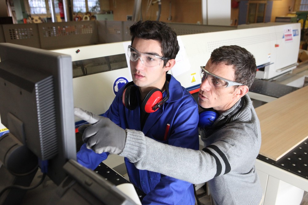 Image of a working helping another worker learn how to use equipment