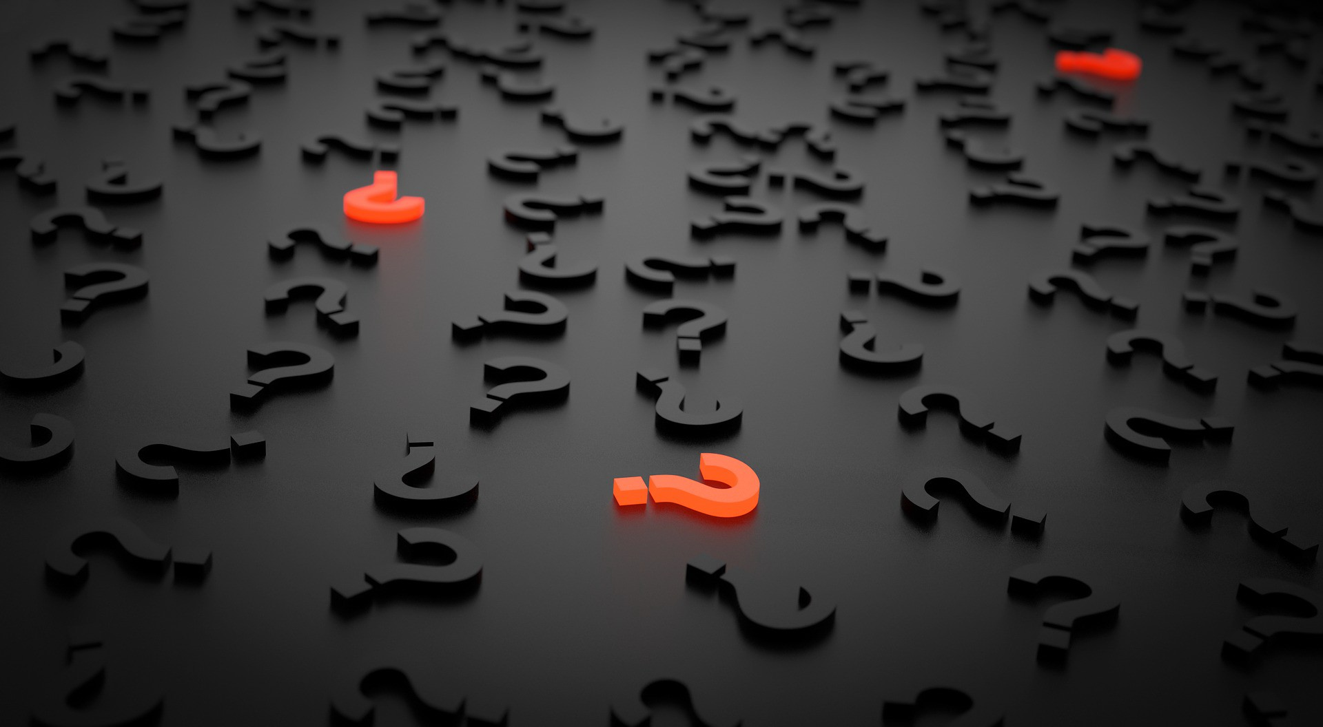A lot of question marks scattered on a table. 3?'s are highlighted in orange while the rest are black.