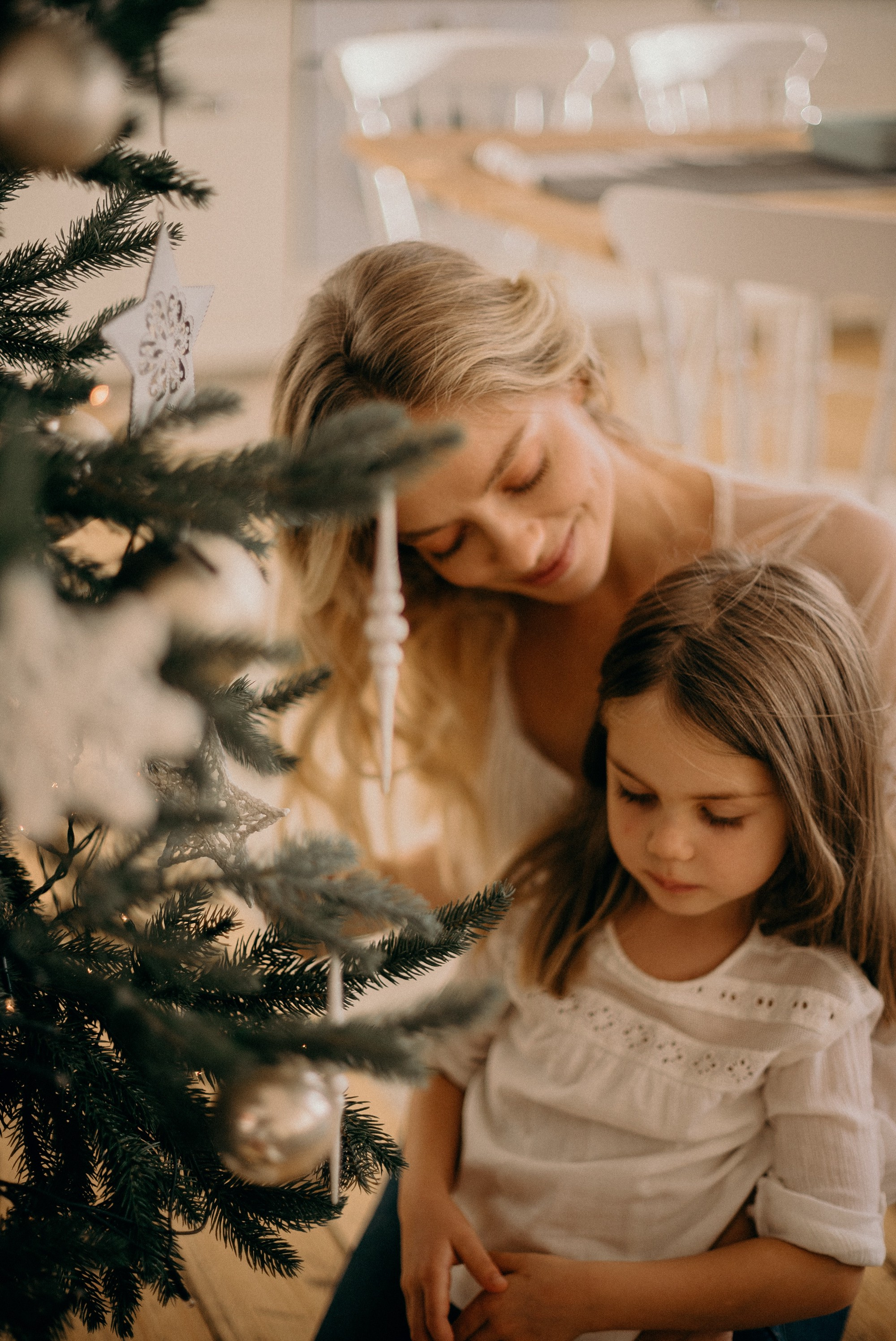 Mother and daughter decorating Christmas tree.