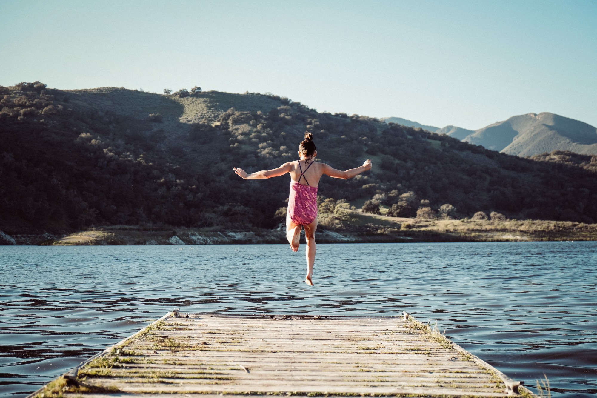 Girl in pink swimming costume jumping into a lake. Mountains are behind her.