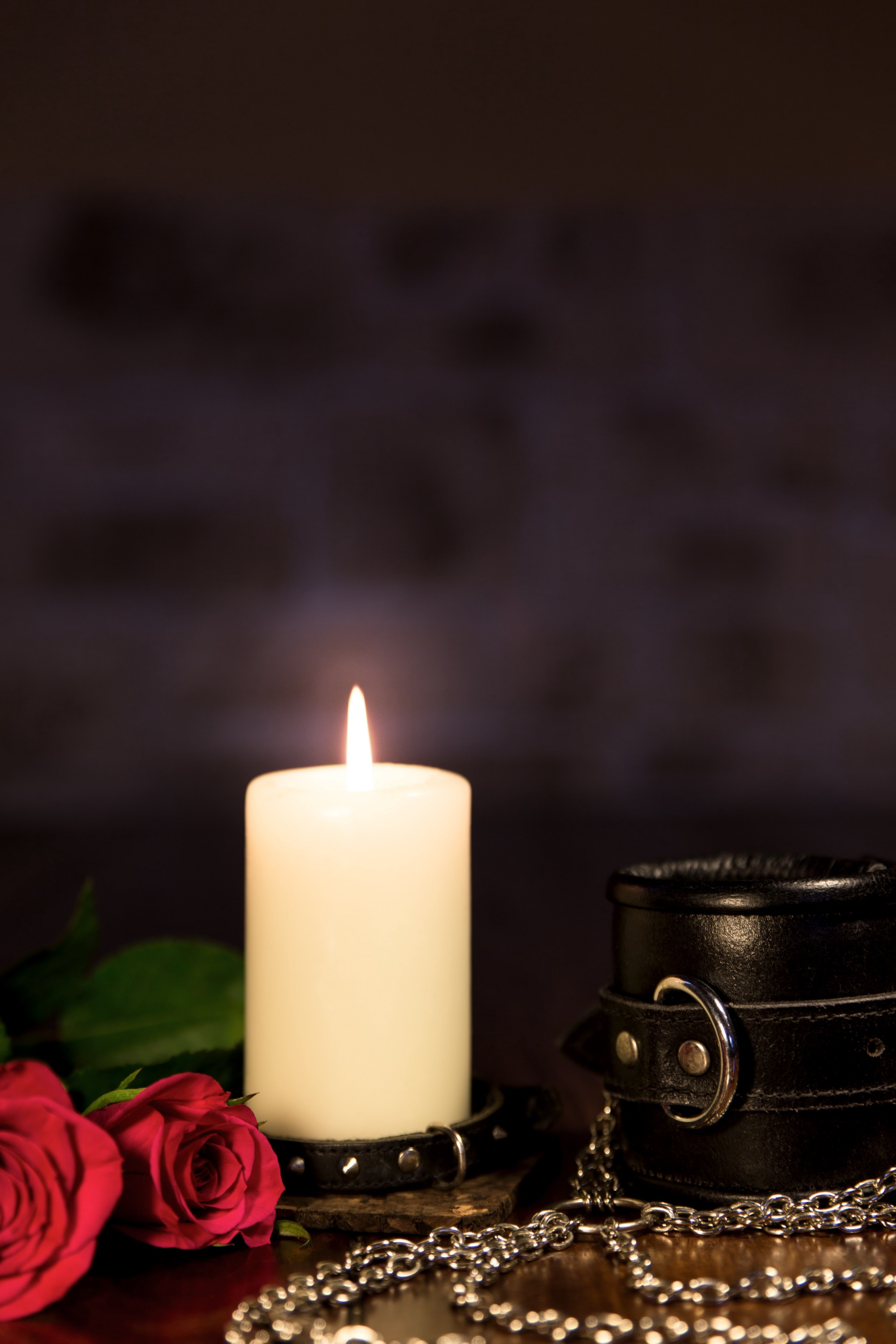 lit candle with bdsm accroutements