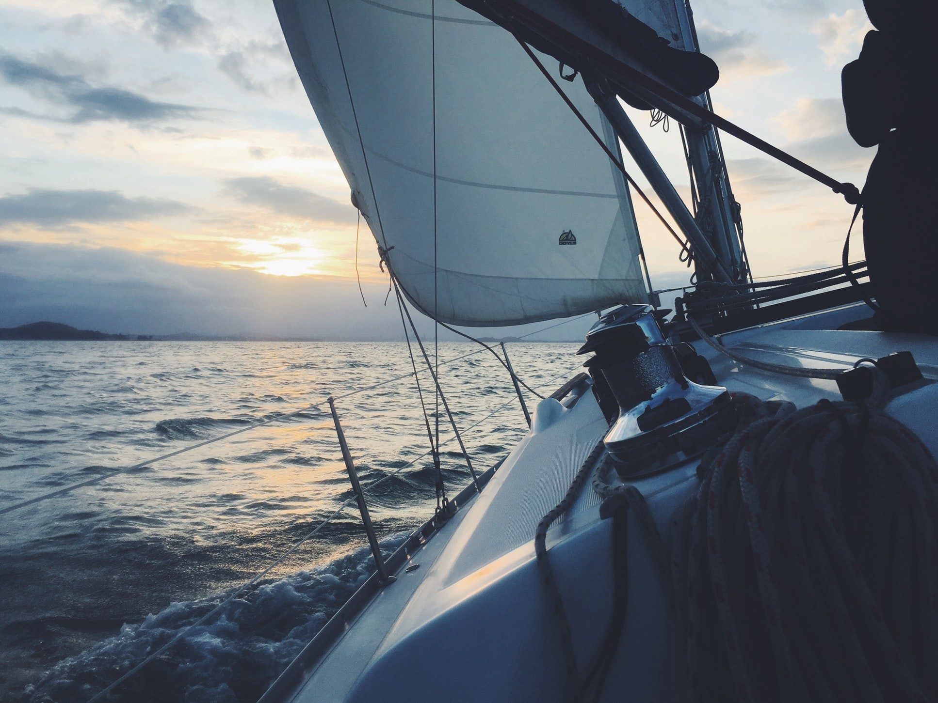 View of a headland at dusk from under the foresail of a yacht on starboard tack.