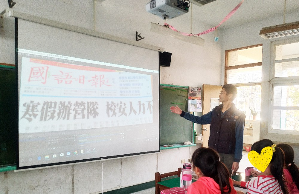 Students reading the same copy of a Chinese newspaper together, projected by a refurbished document camera.