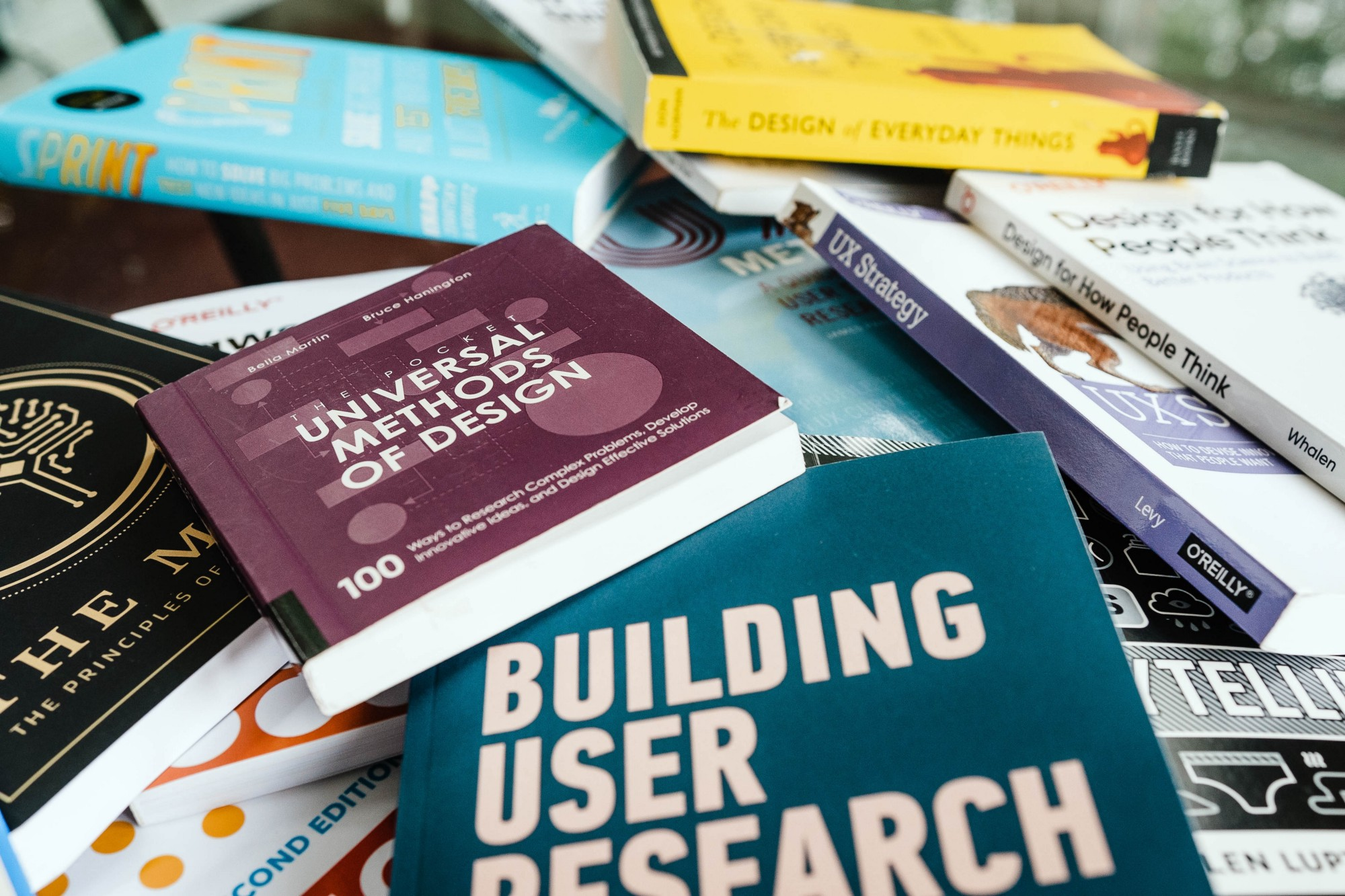 A messy pile of books about UX, including Universal Methods of Design and Building User Research