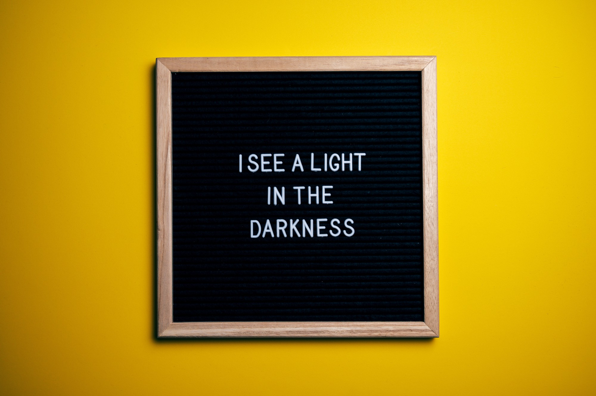 a board on the wall that reads i see a light in the darkness