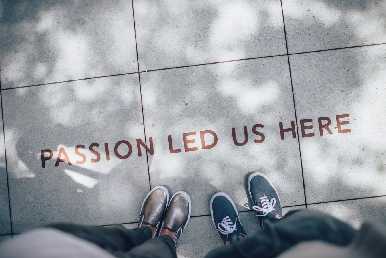 Two sets of feet standing right in front of a quote written on the floor that reads: Passion led us here.