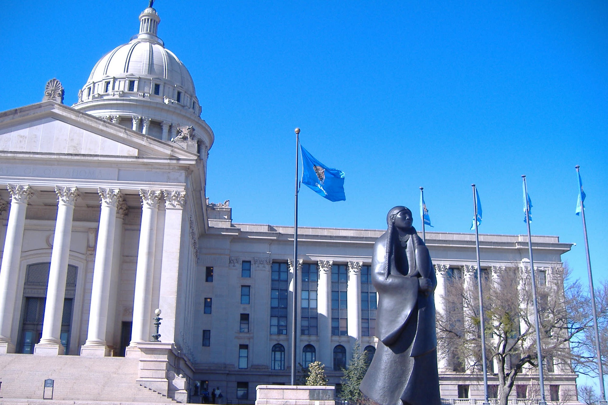 Bronze sculpture of a Native American woman in front of the neoclassical facade of the Oklahoma State Capitol building.