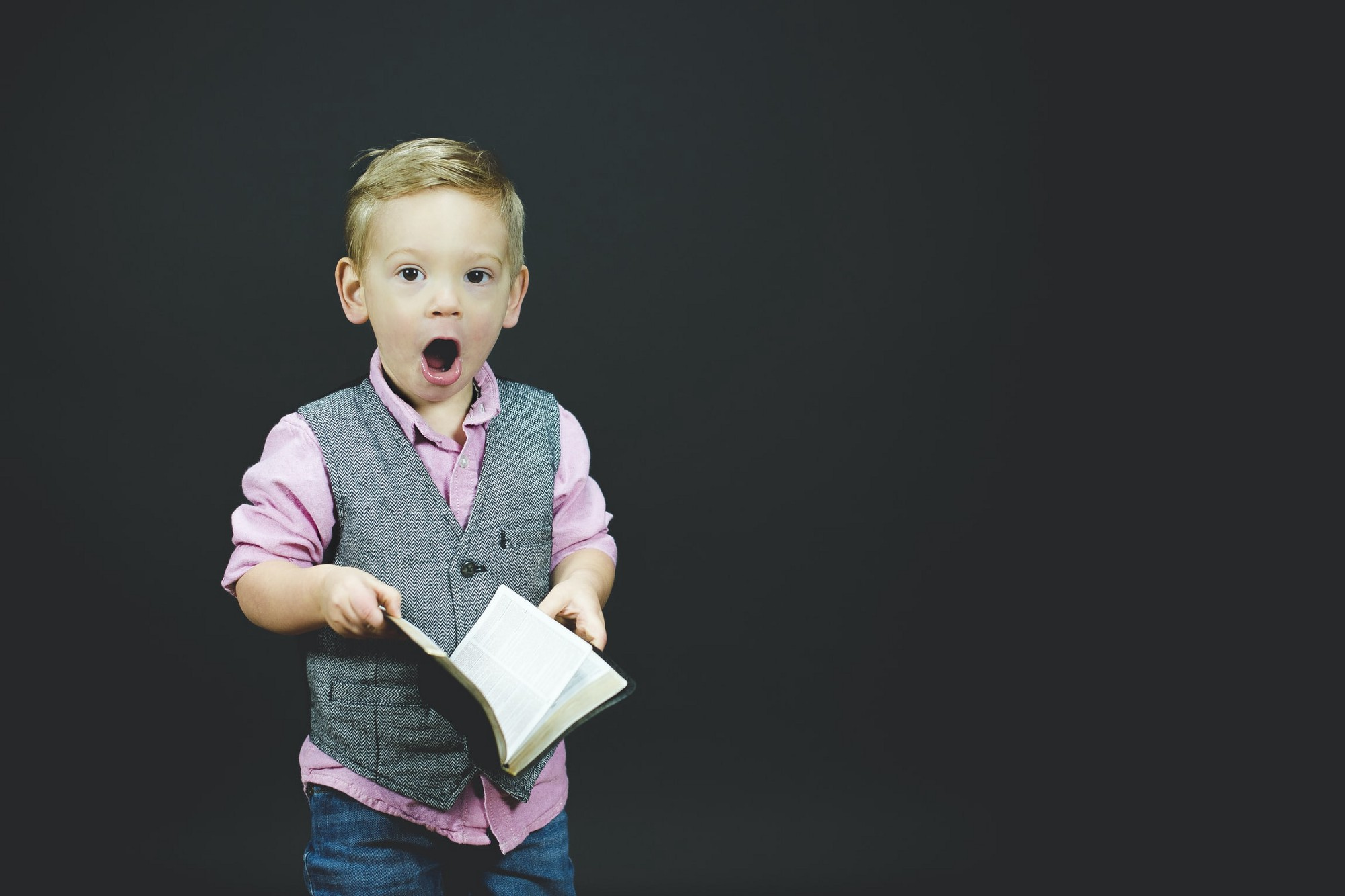Boy with his mouth open while holding a book.