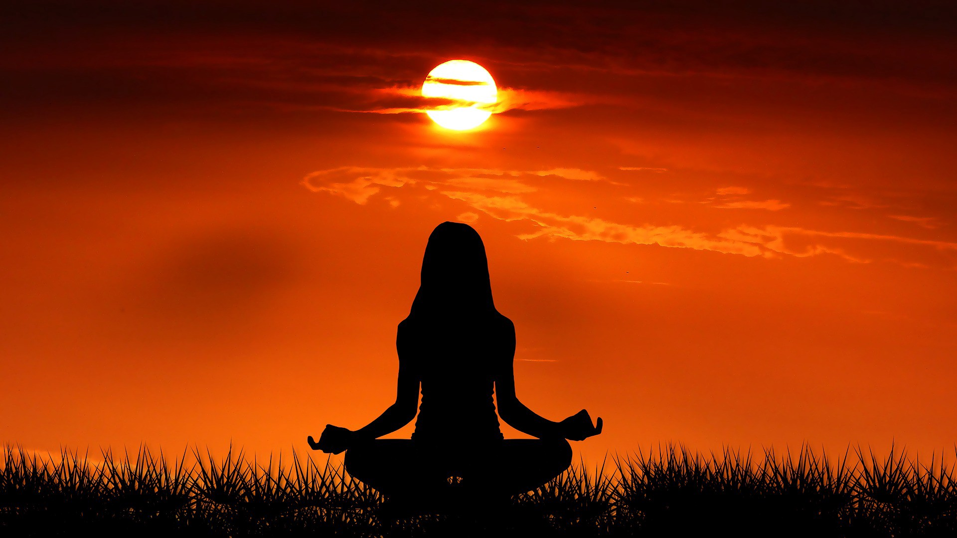 A girl doing meditation in front of a sunrise