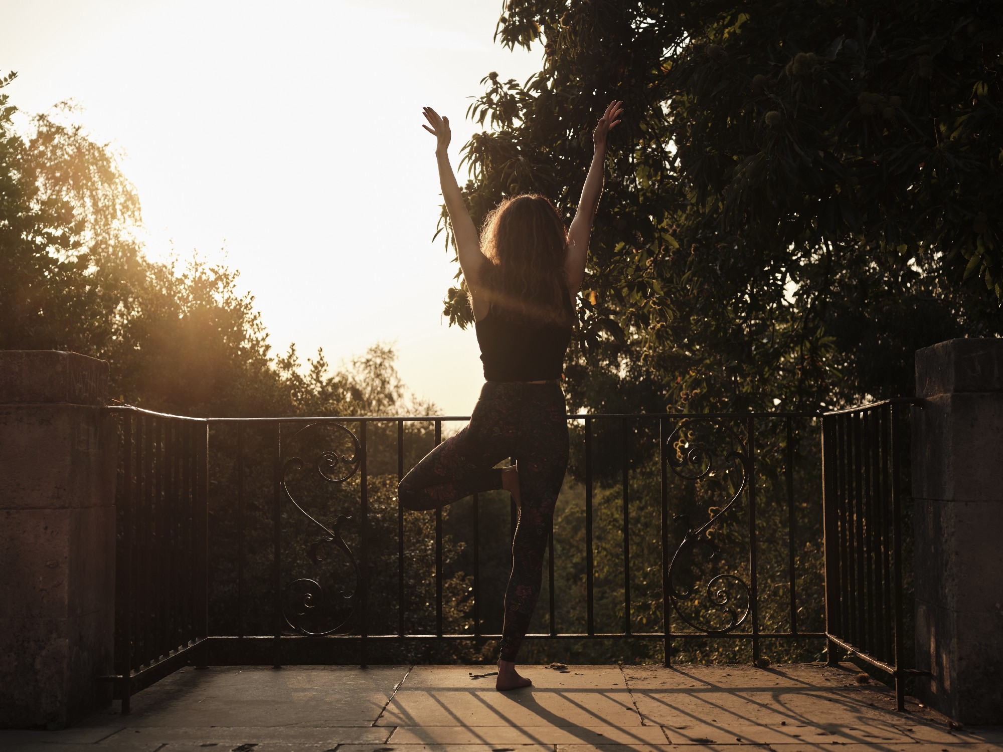Woman in yoga pants standing in tree pose at sunset