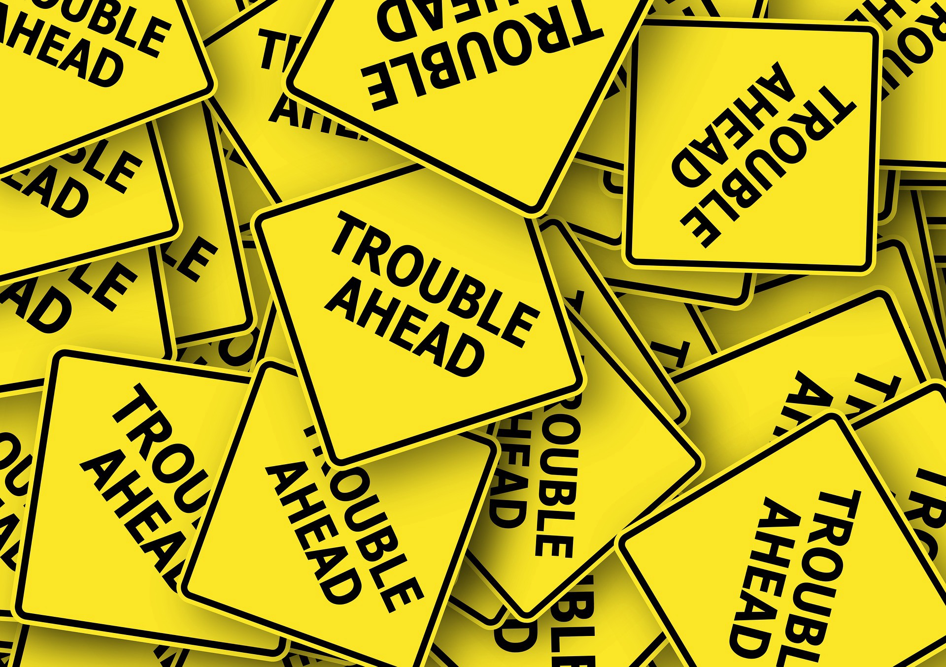 Yellow signs saying Trouble Ahead
