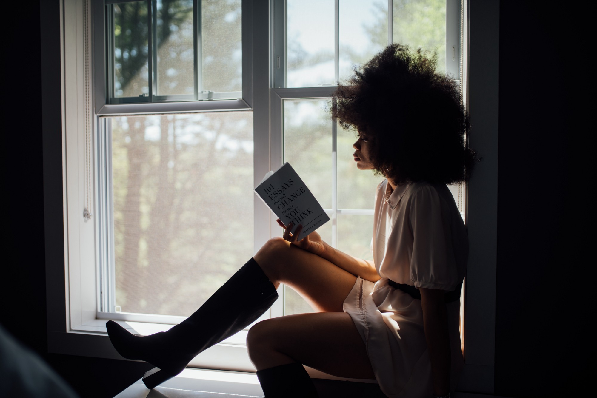 """A Black Woman sitting in a window sill reading, """"101 Essays that will change the way you think."""""""