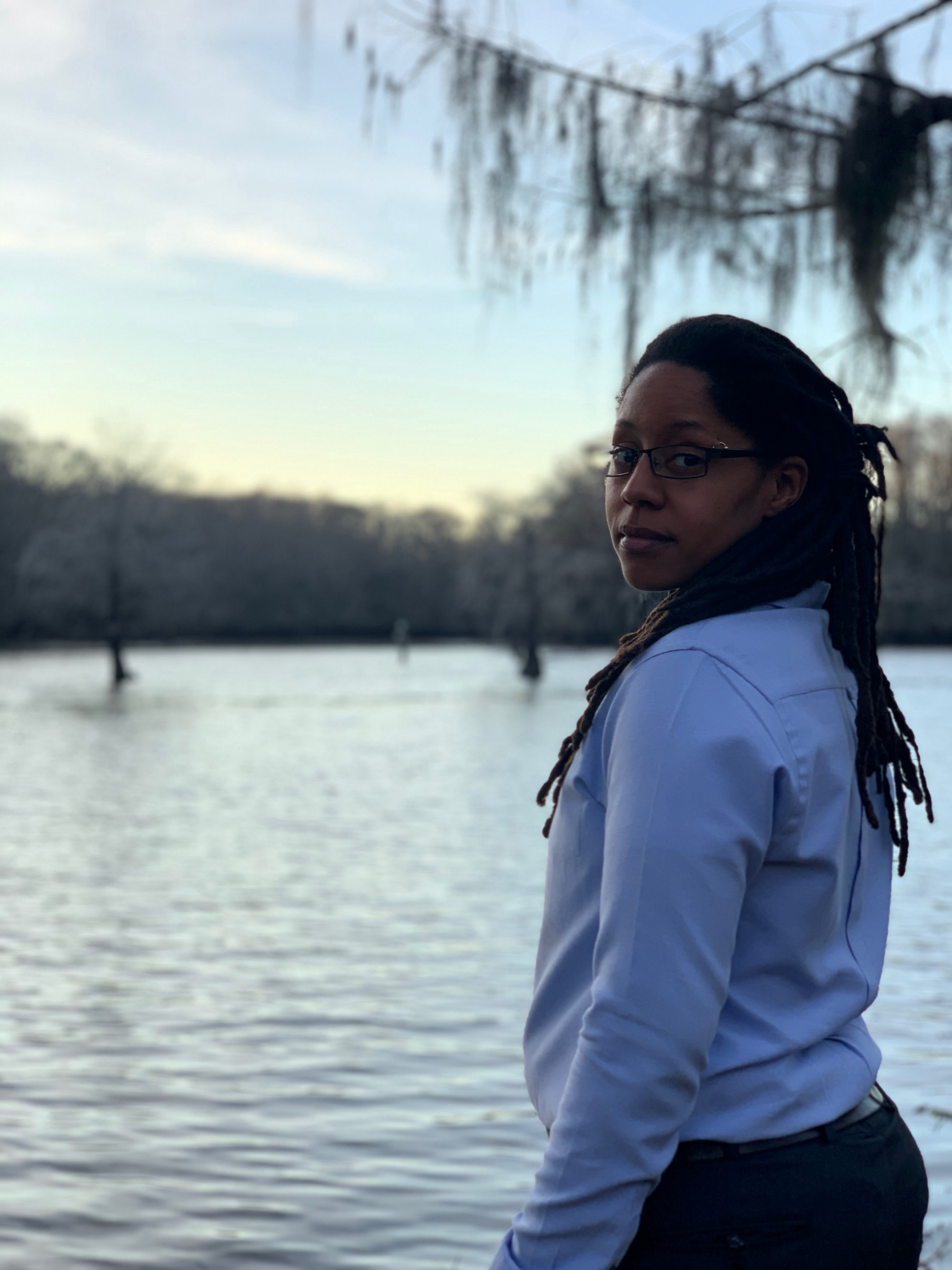 A photo of Richael, looking over their shoulder, with hanging dreadlocks on their dress shirt, with Caddo Lake behind.