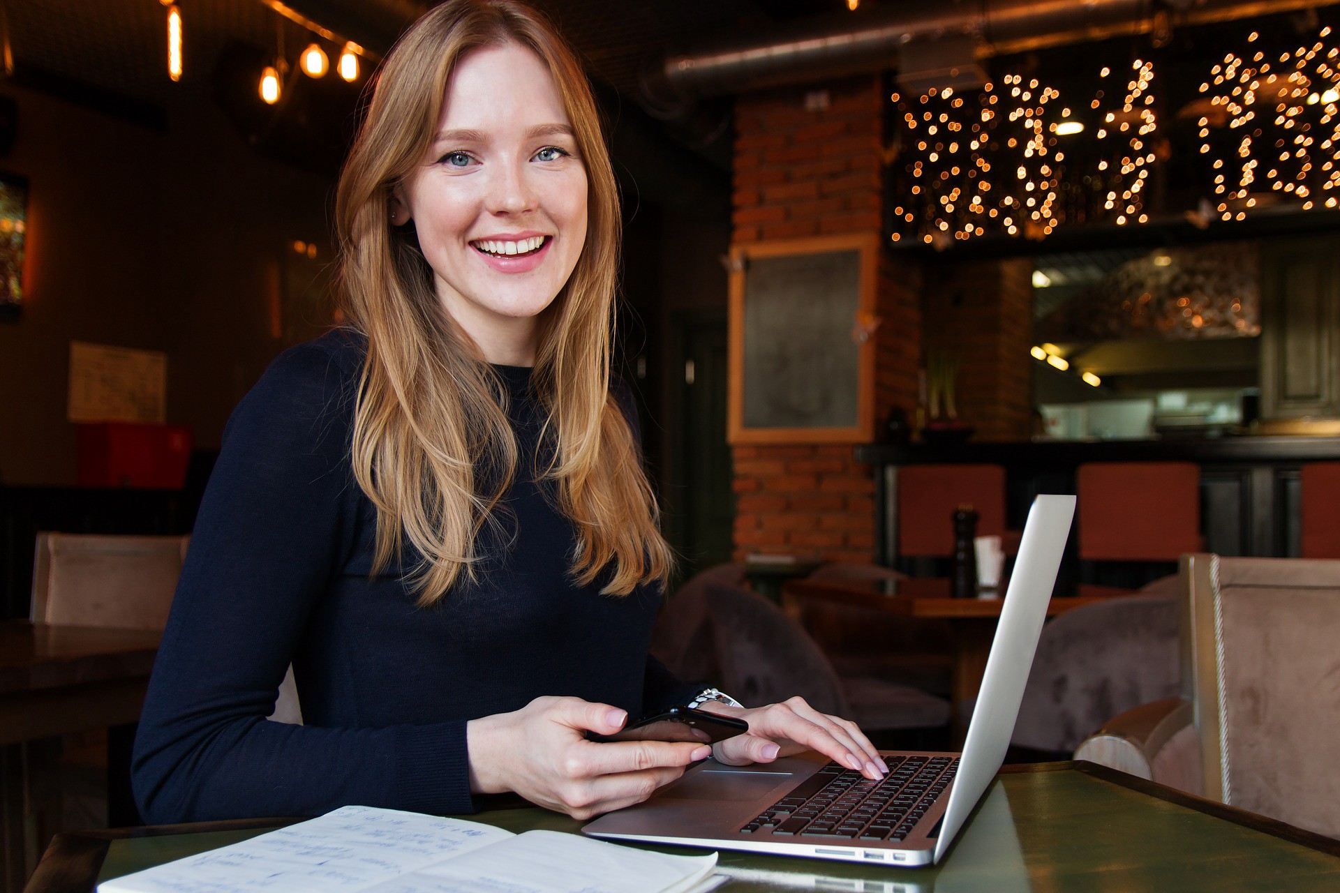 Young woman in font of a laptop smiling at the camera.
