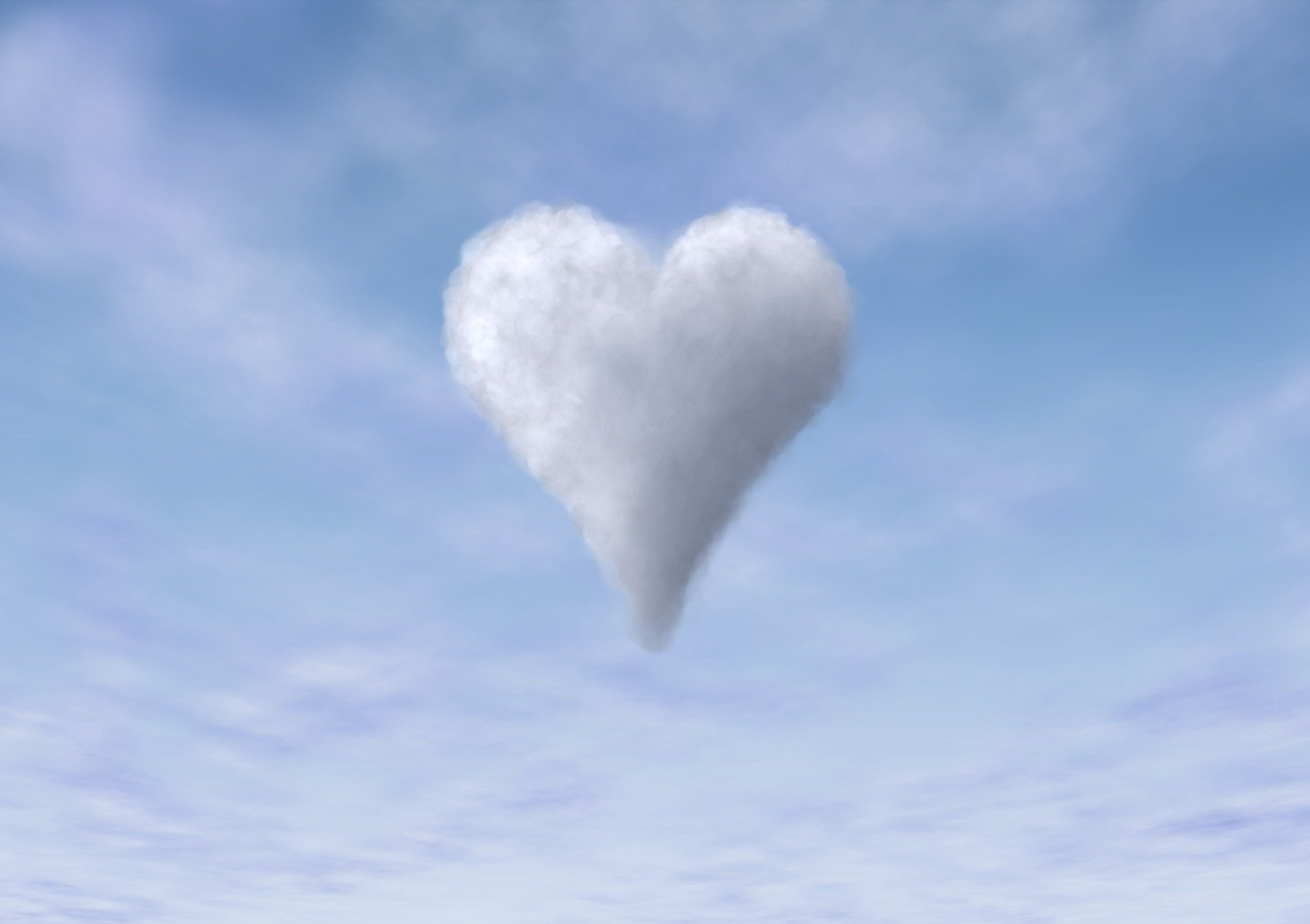 A white heart shaped cloud in a baby blue sky