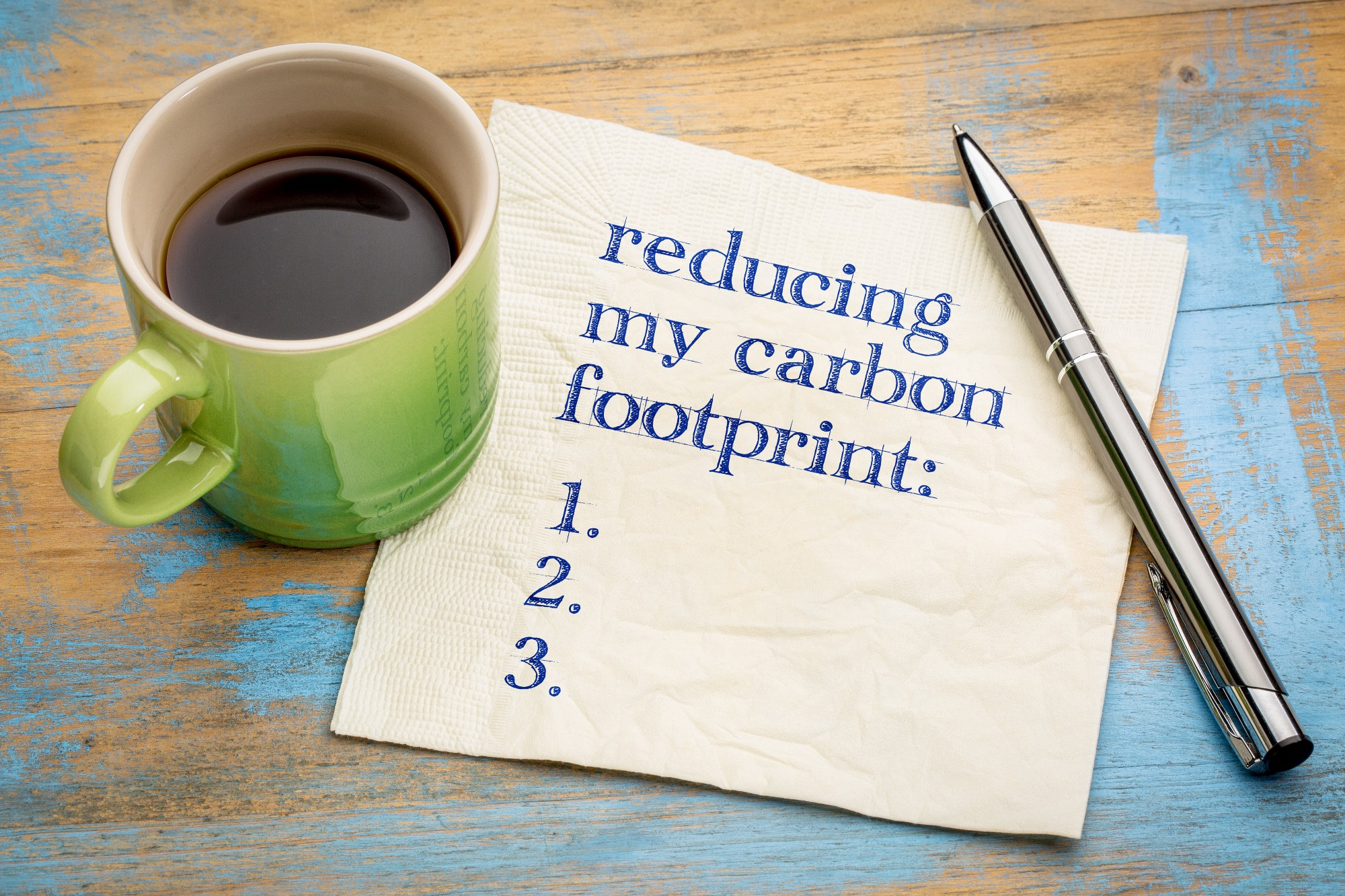 A picture of a coffee cup and a napkin that says 'reducing my carbon footprint: 1. 2. 3.'