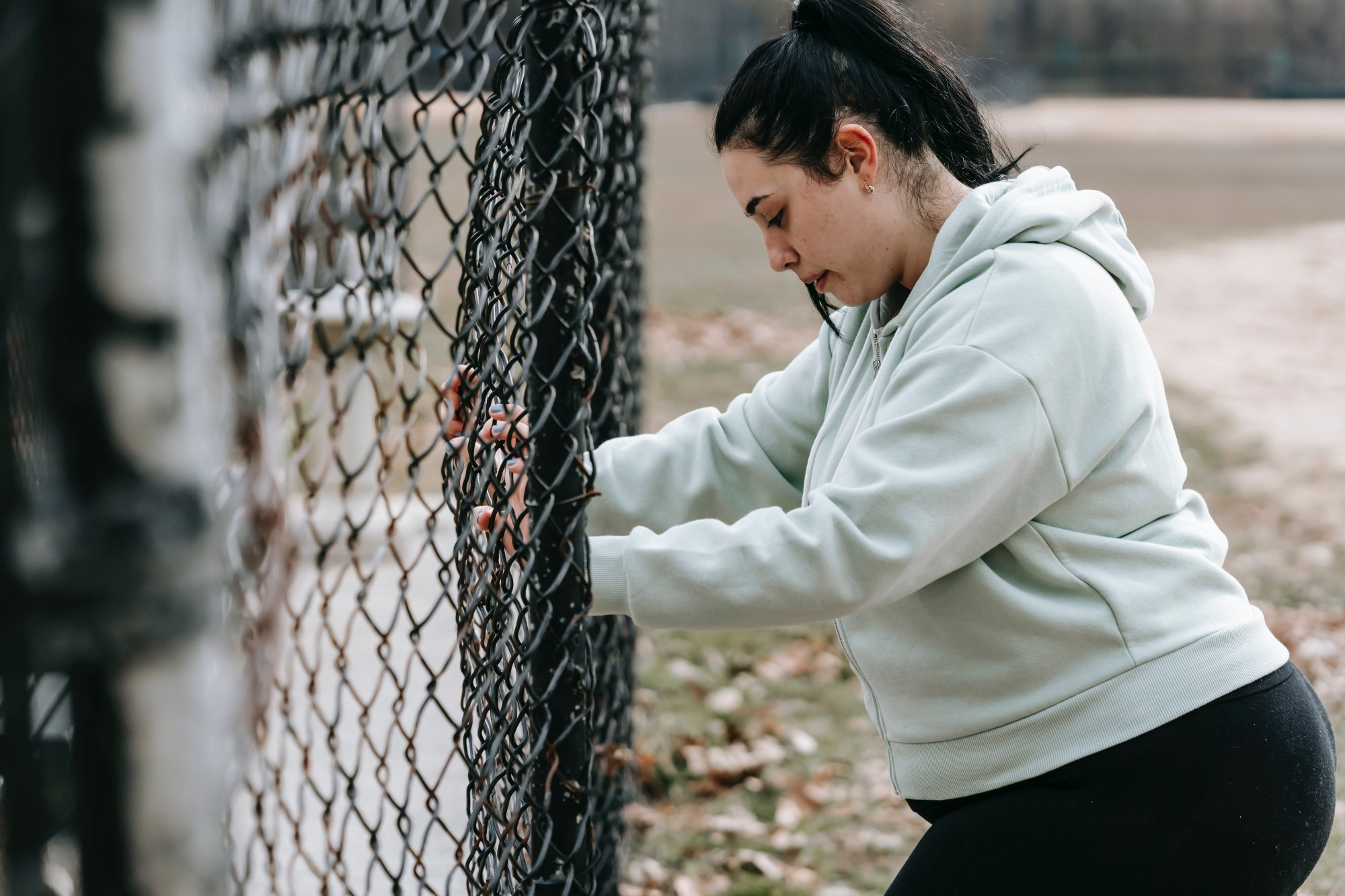 Image of a woman in workout gear looking pensive by a fence