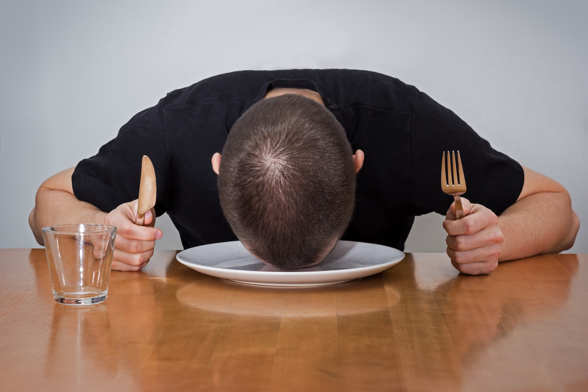 A person holding a fork and knife at a dinner table, resting their head on an empty plate.