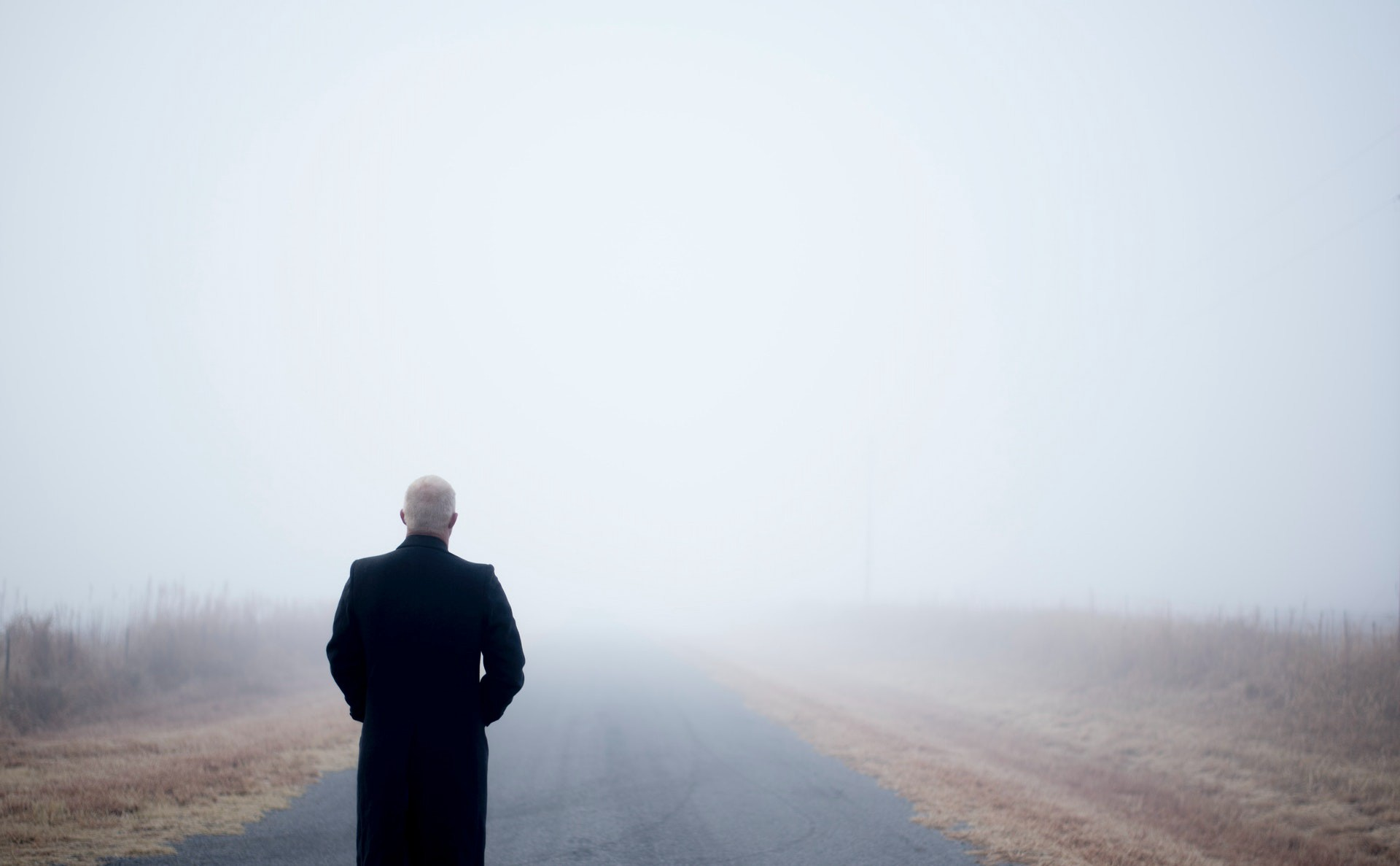 Man looking out at a foggy road