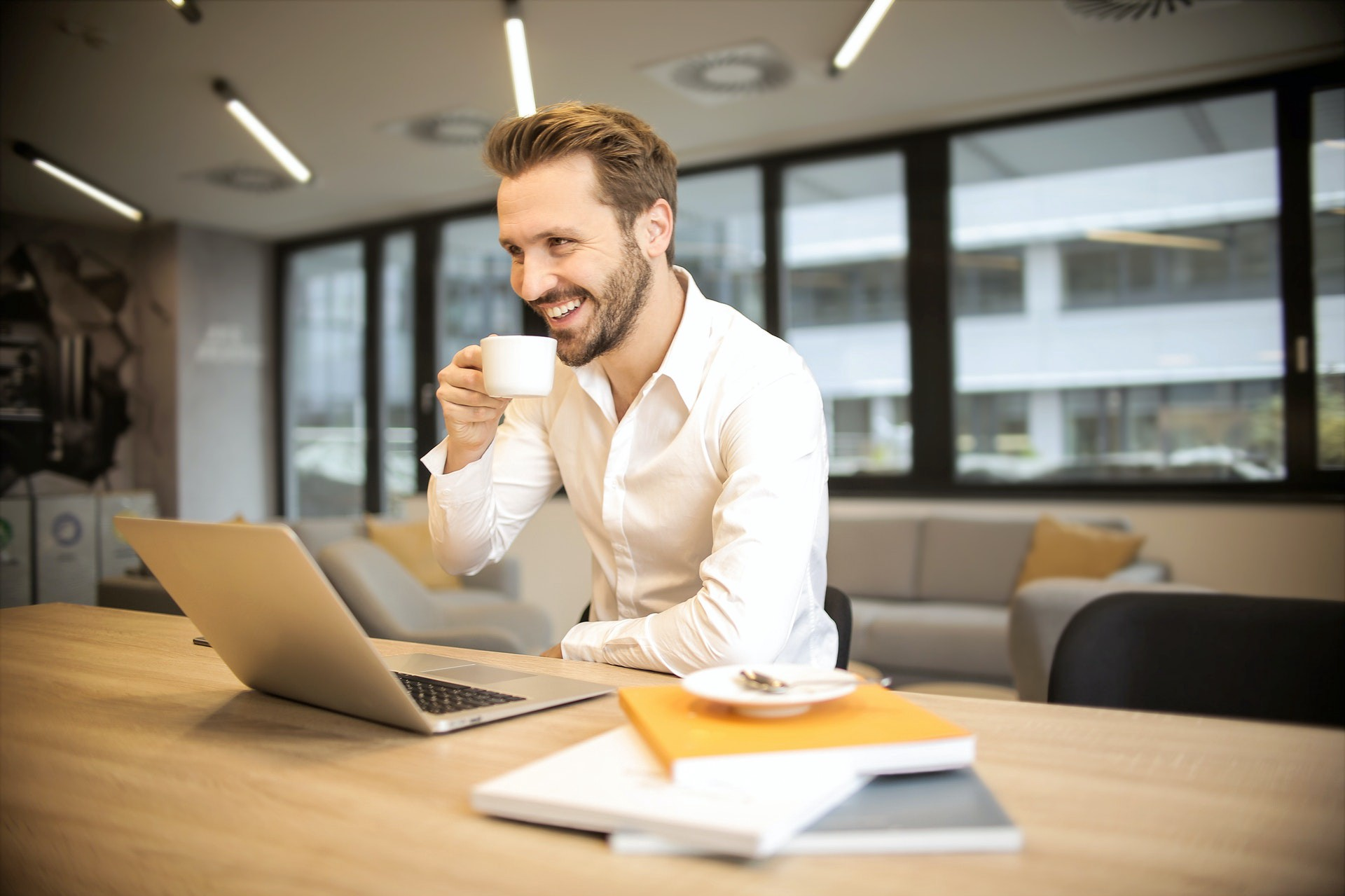 man in front of a computer holding cup of coffee and smiling.