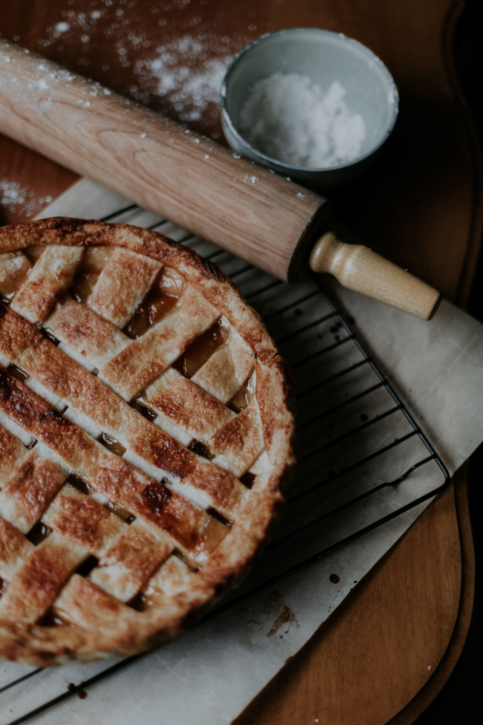 Photo of homemade apple pie with roller pin and flour