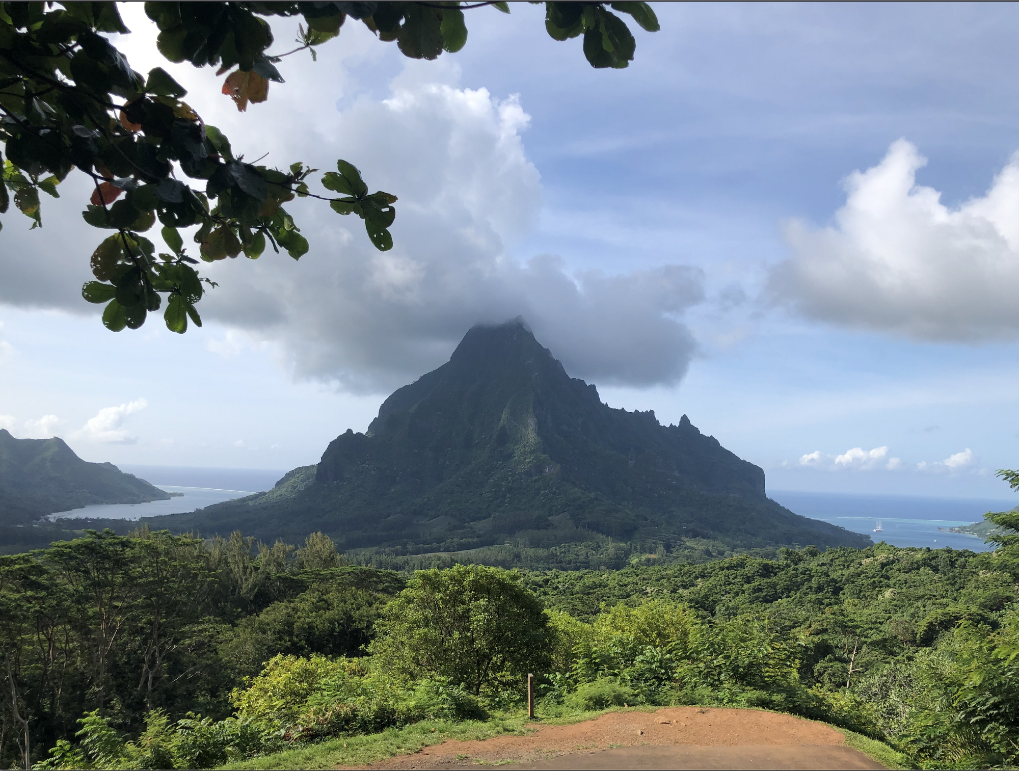 A landscape view of a tropical mountain in the distance surrounded by clouds and the ocean.