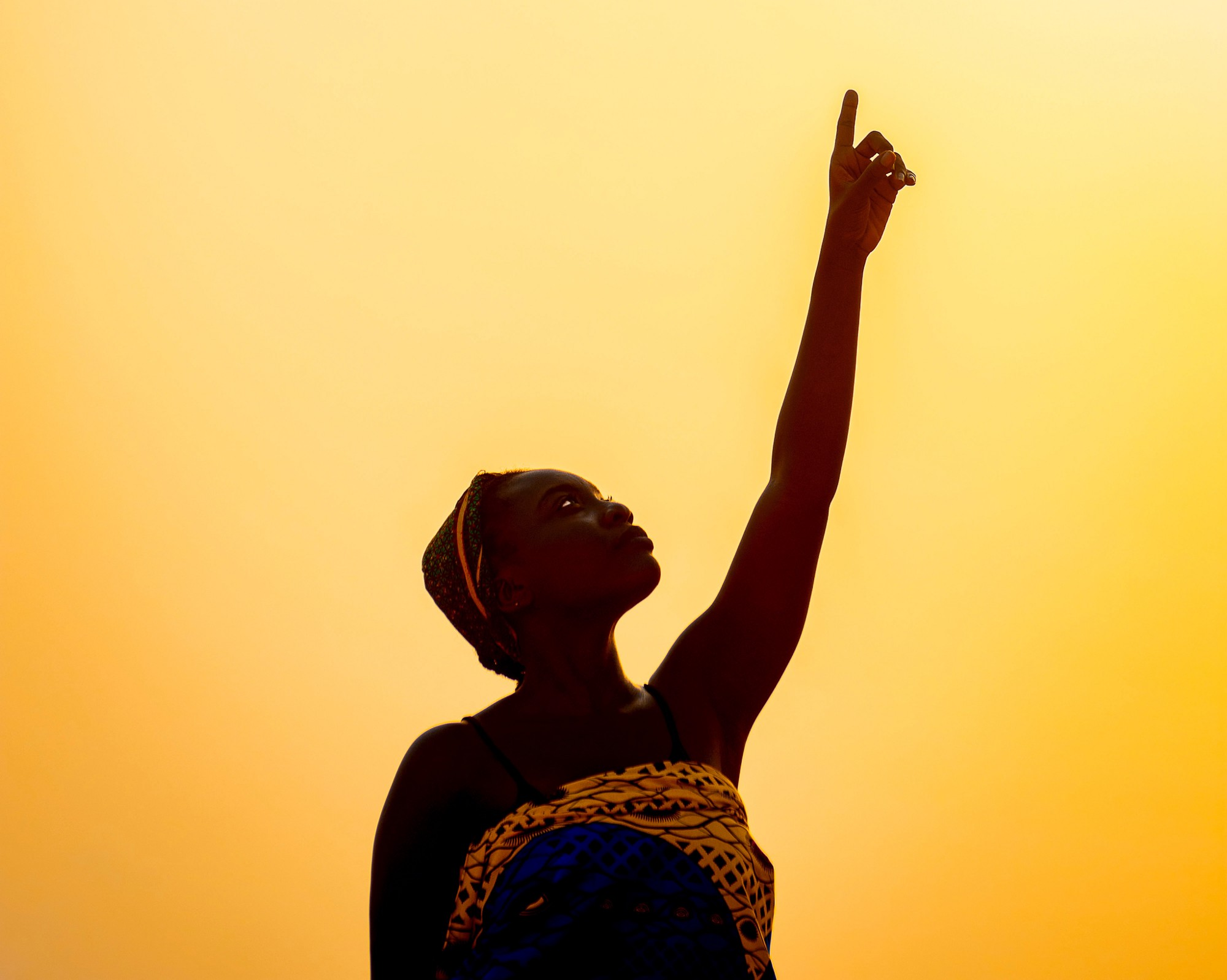 Woman pointing at the sun during a golden sunset.