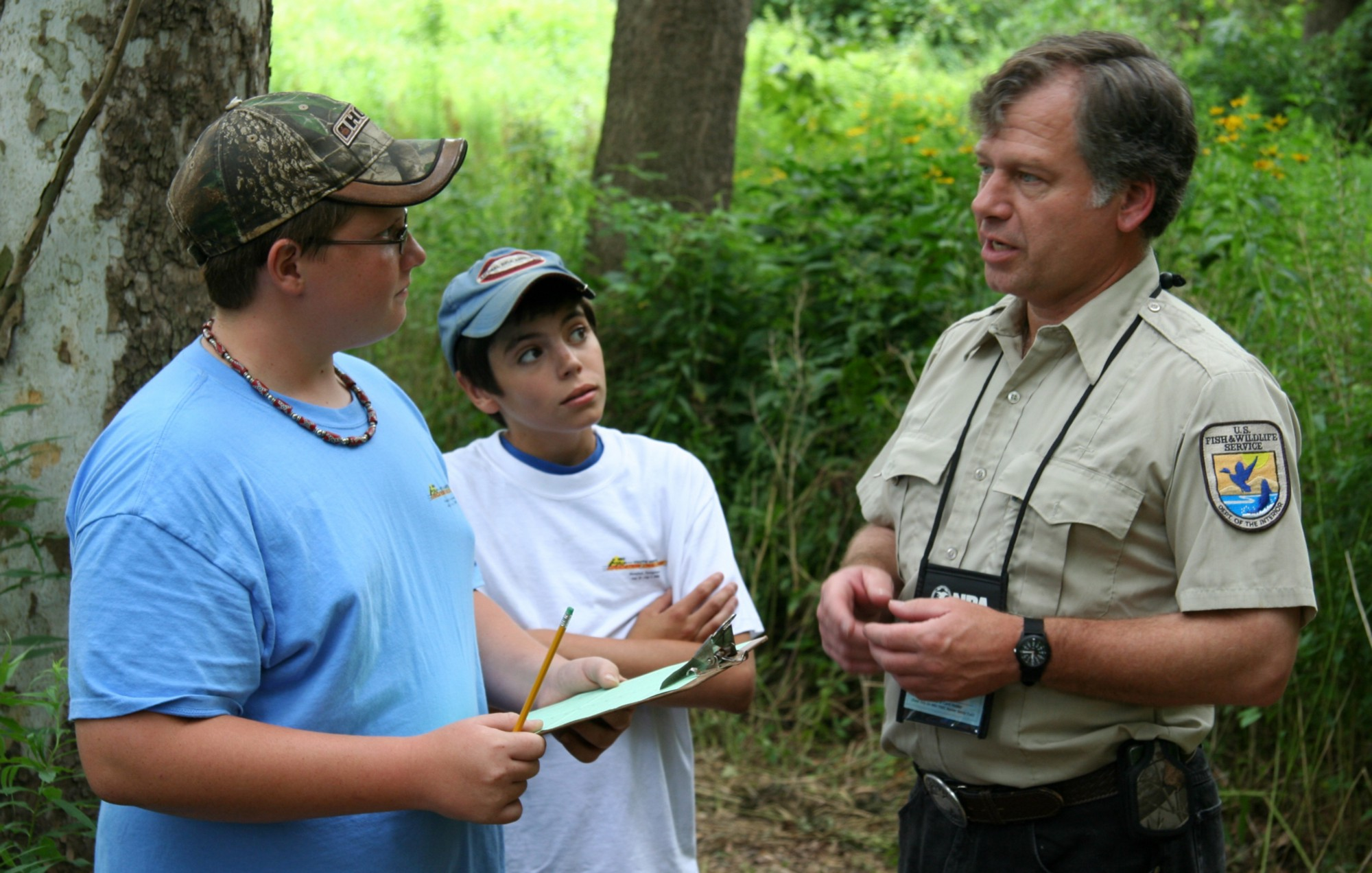 Bill Vogel, a USFWS biologist, speaks to two students about hunting.
