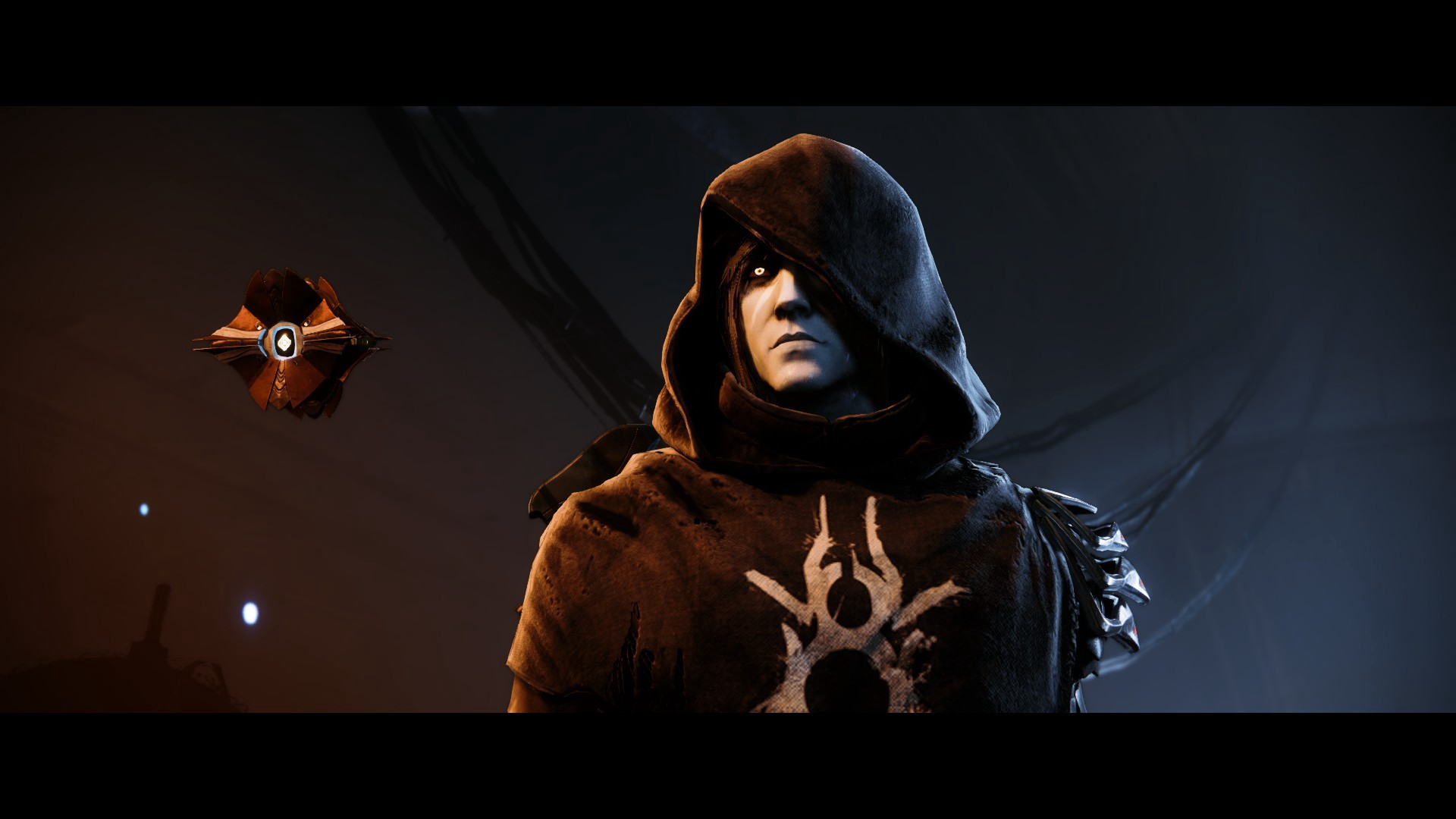 A screenshot of Crow from Destiny 2, a young man with grey skin and glowing yellow eyes wearing a black hooded cloak, with his Ghost, a small floating drone, by his side.