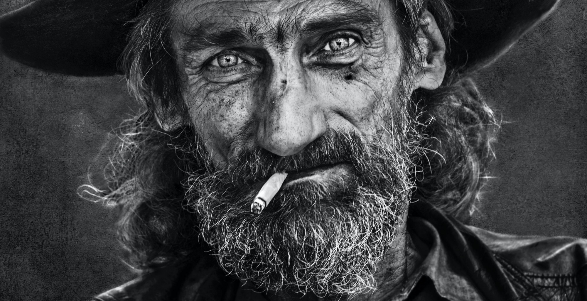 Stunning black and white image of an aged man with a beard and burning cigarette