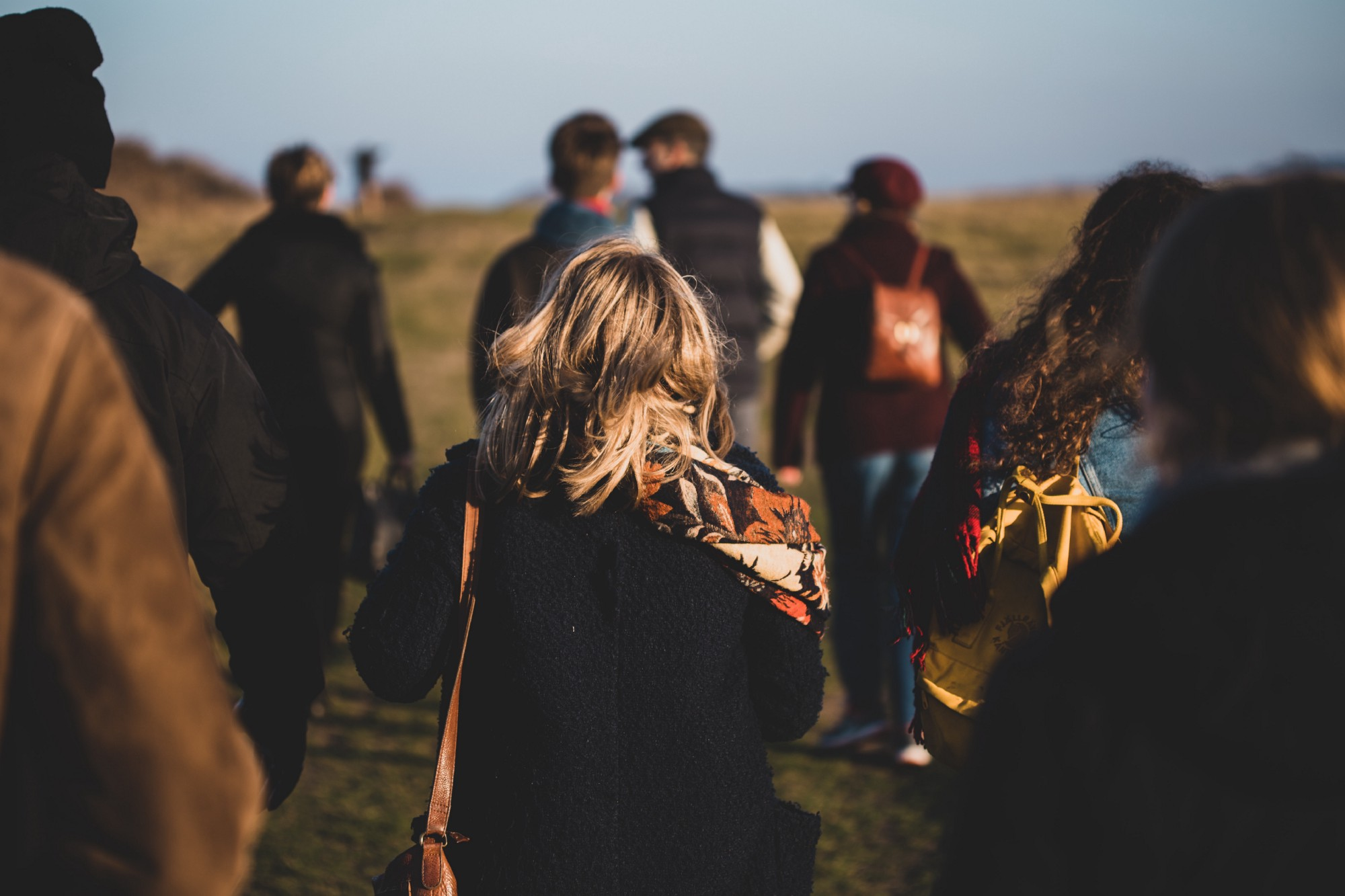Photo of a group of people, in coats and scarves, walking up a field. The focus is soft around the edges, and only the person in the center is clear—black coat, orange patterned scarf, tousled blond hair around their shoulders.