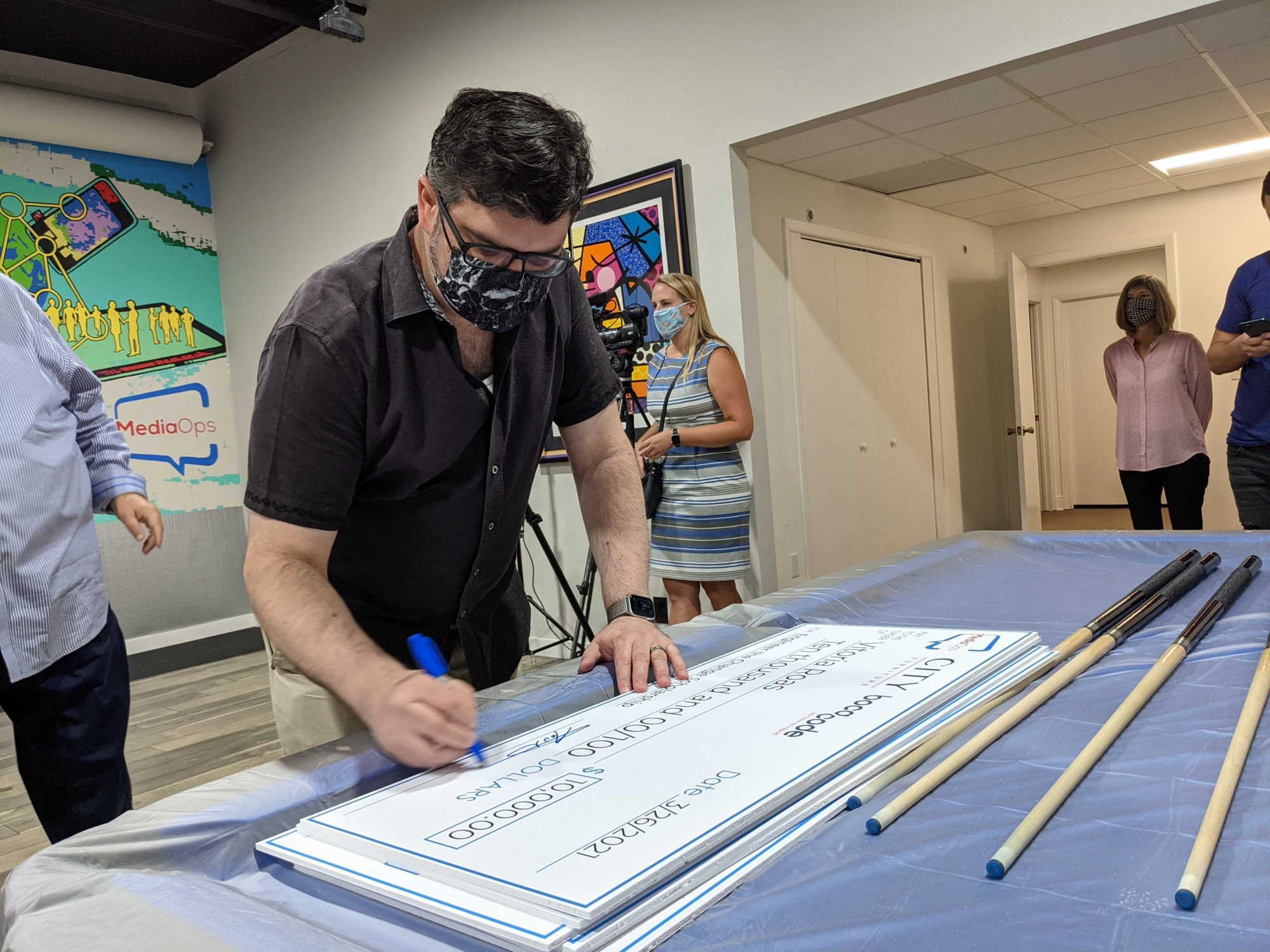 Todd Albert leans over a pool table at MediaOps headquarters to sign a giant scholarship check.