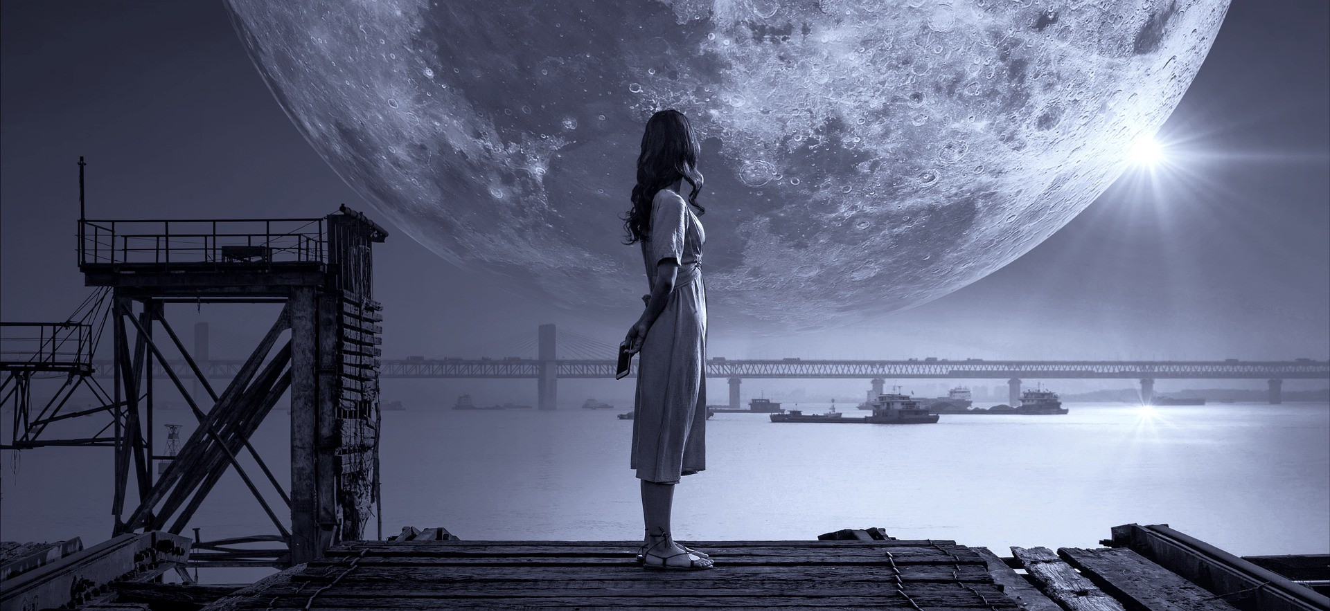 Girl watching moon on a dock at night