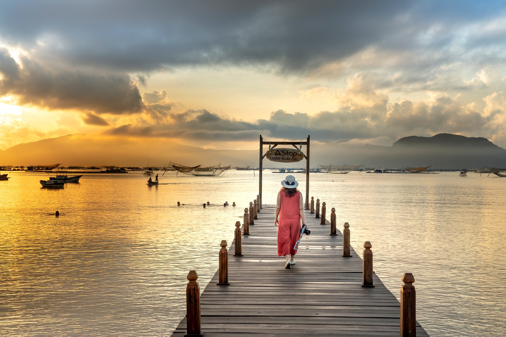 Back view of woman in pink outfit walking on dock during sunset