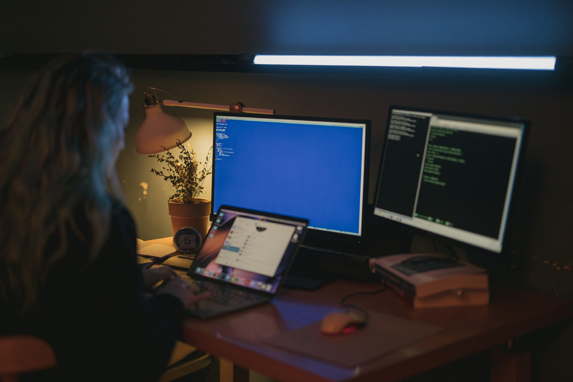 Woman coding with two monitors and a laptop