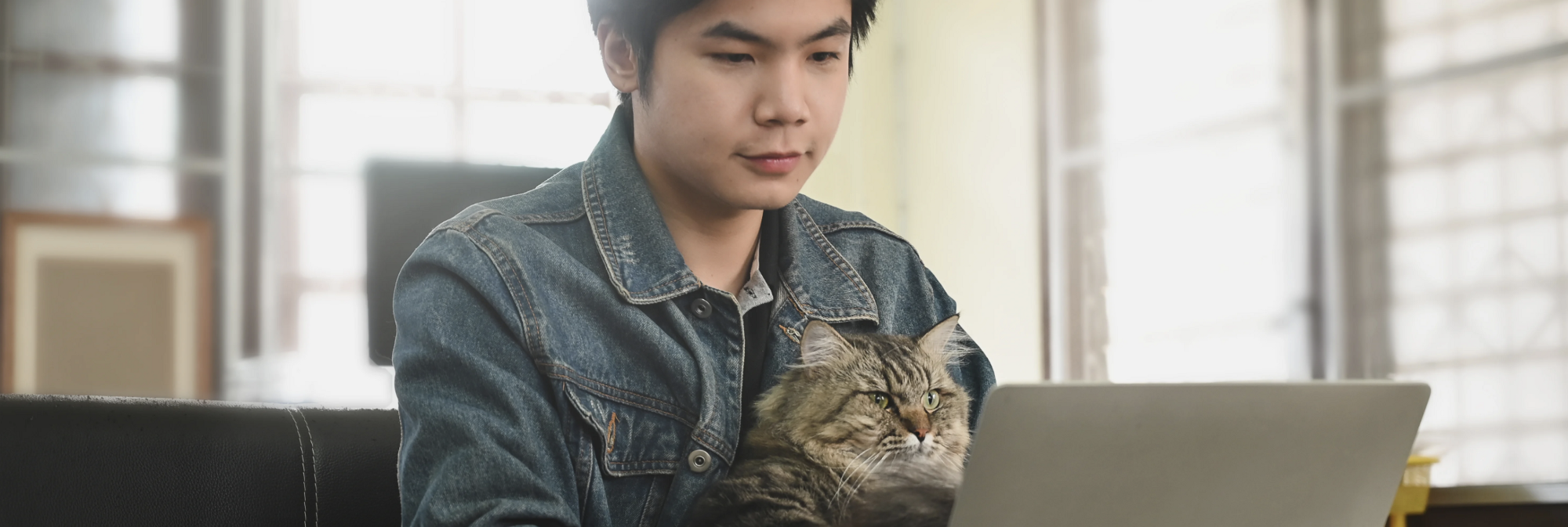 Man in denim jacket sits behind laptop with grey striped cat on his lap.