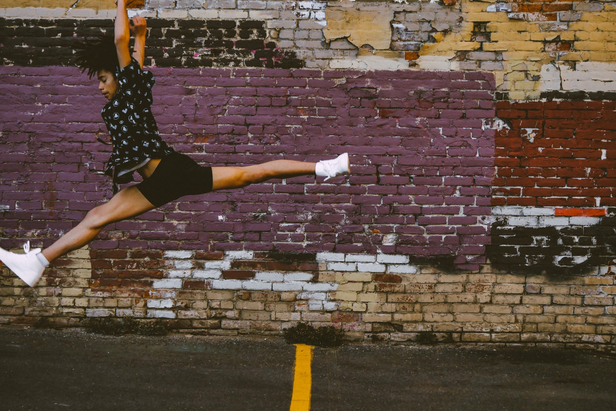 black woman leaping in front of a brick wall