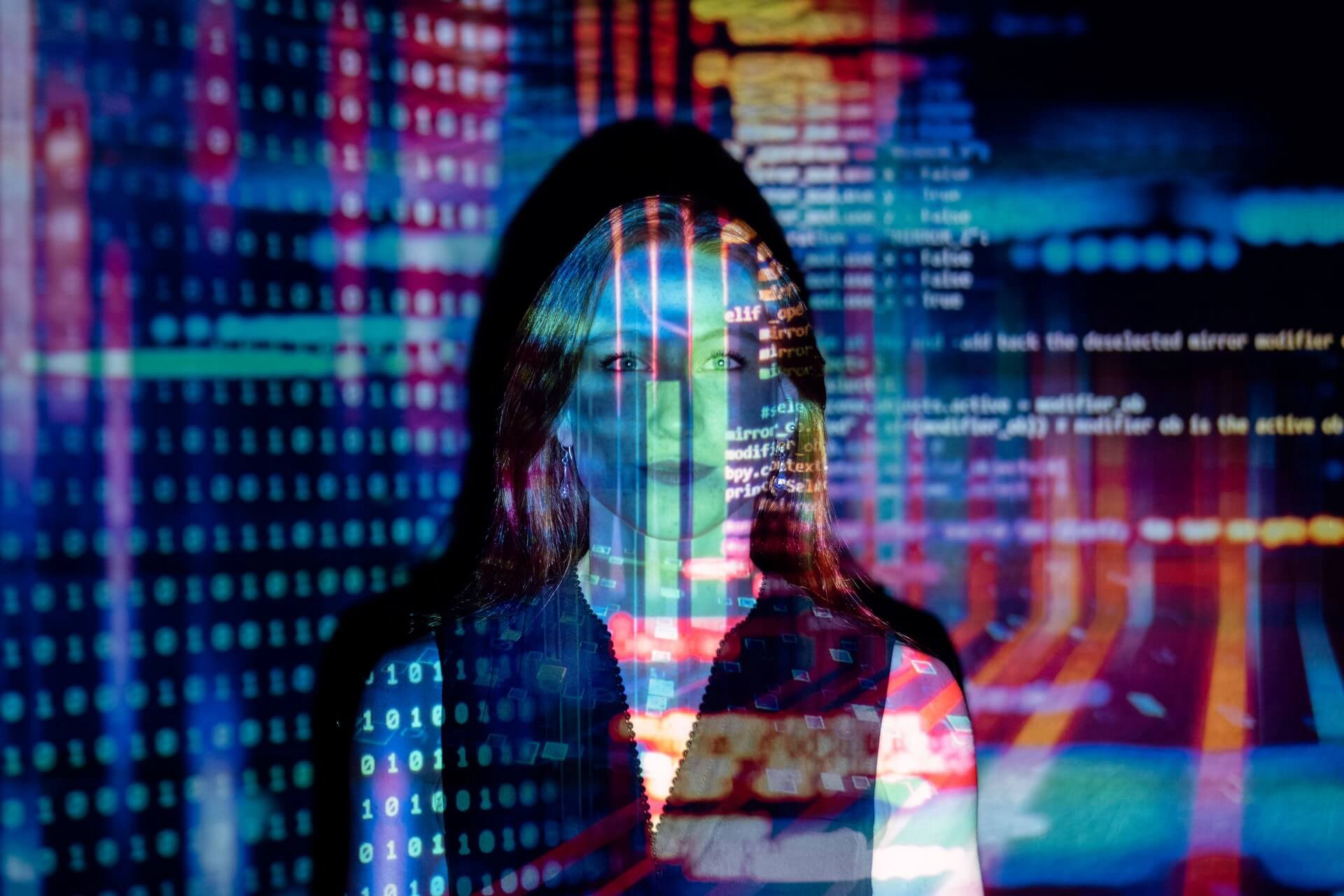 Software engineer stands in her office as lines of code are projected onto her face and the walls of the office.