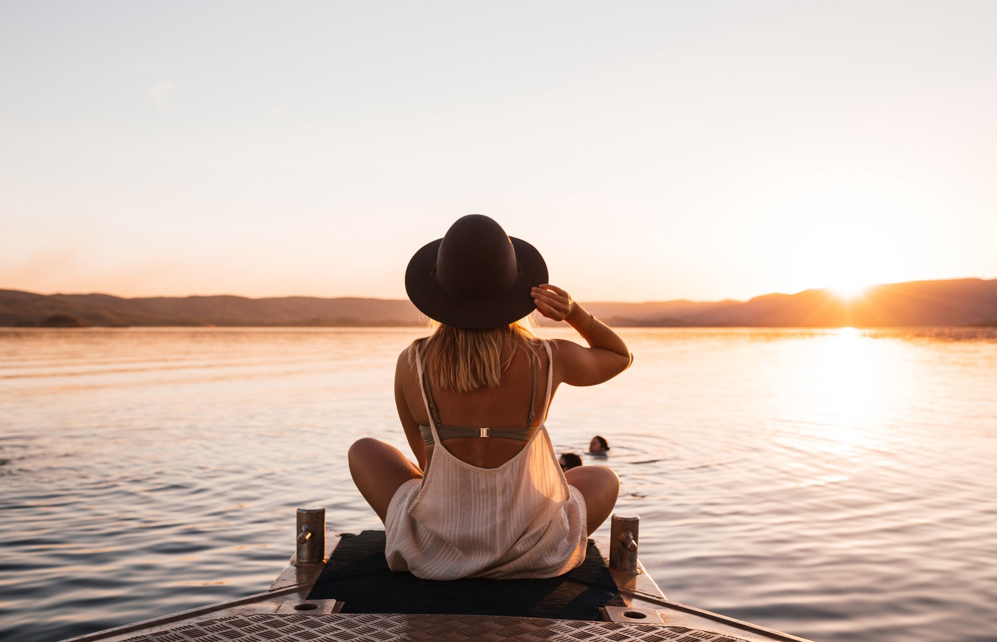 A calm lady sitting on banks of river.