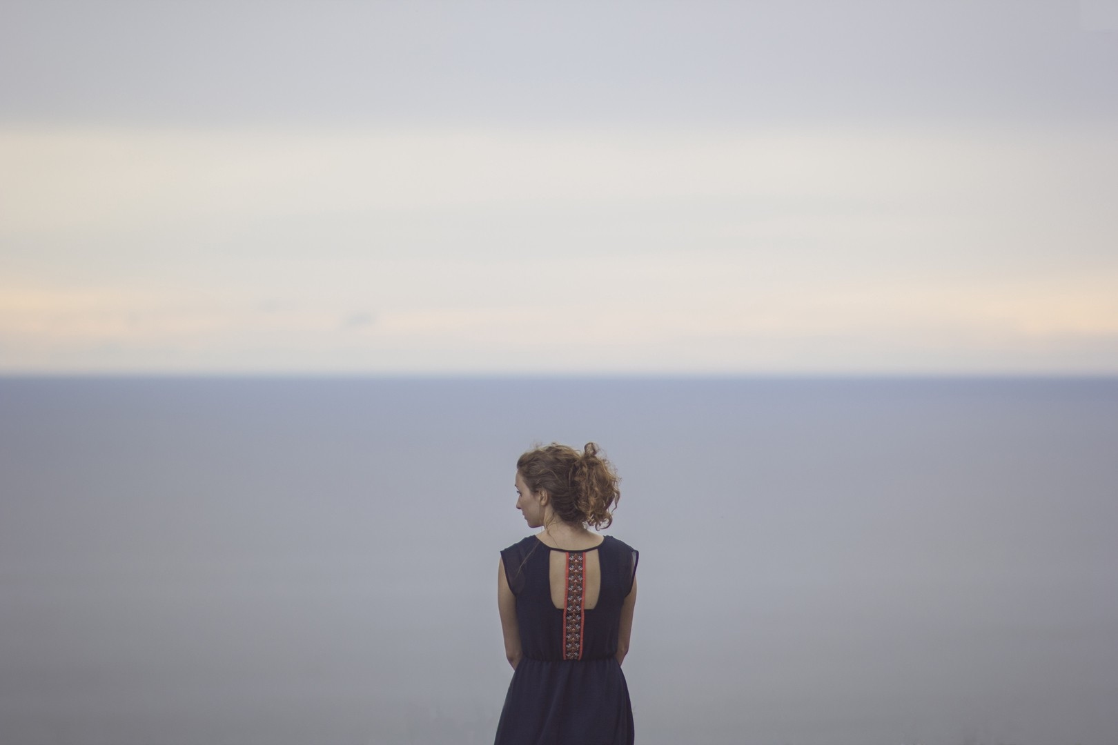 Woman stands in front of a grey ocean with her back to the camera
